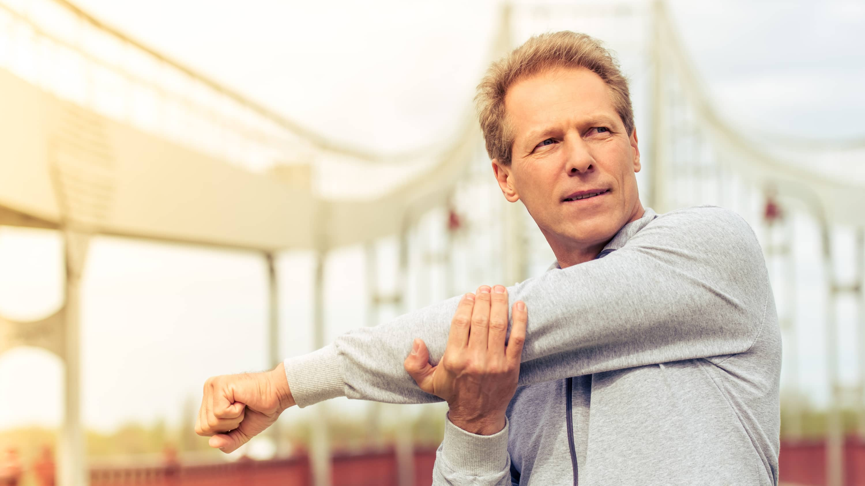 Man stretching before workout, possibly after receiving body-contouring surgery