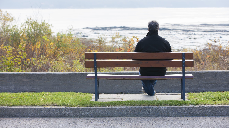 man looking at ocean, possibly after Huntington's disease diagnosis