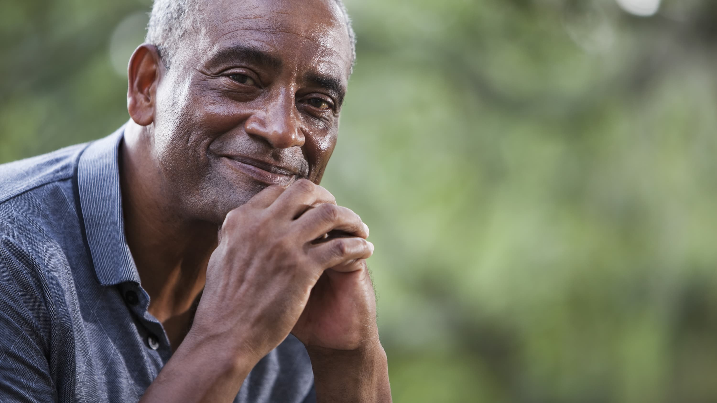 An older man who is holding his hands in front of his face and may be smiling because he had a negative prostate cancer screening .