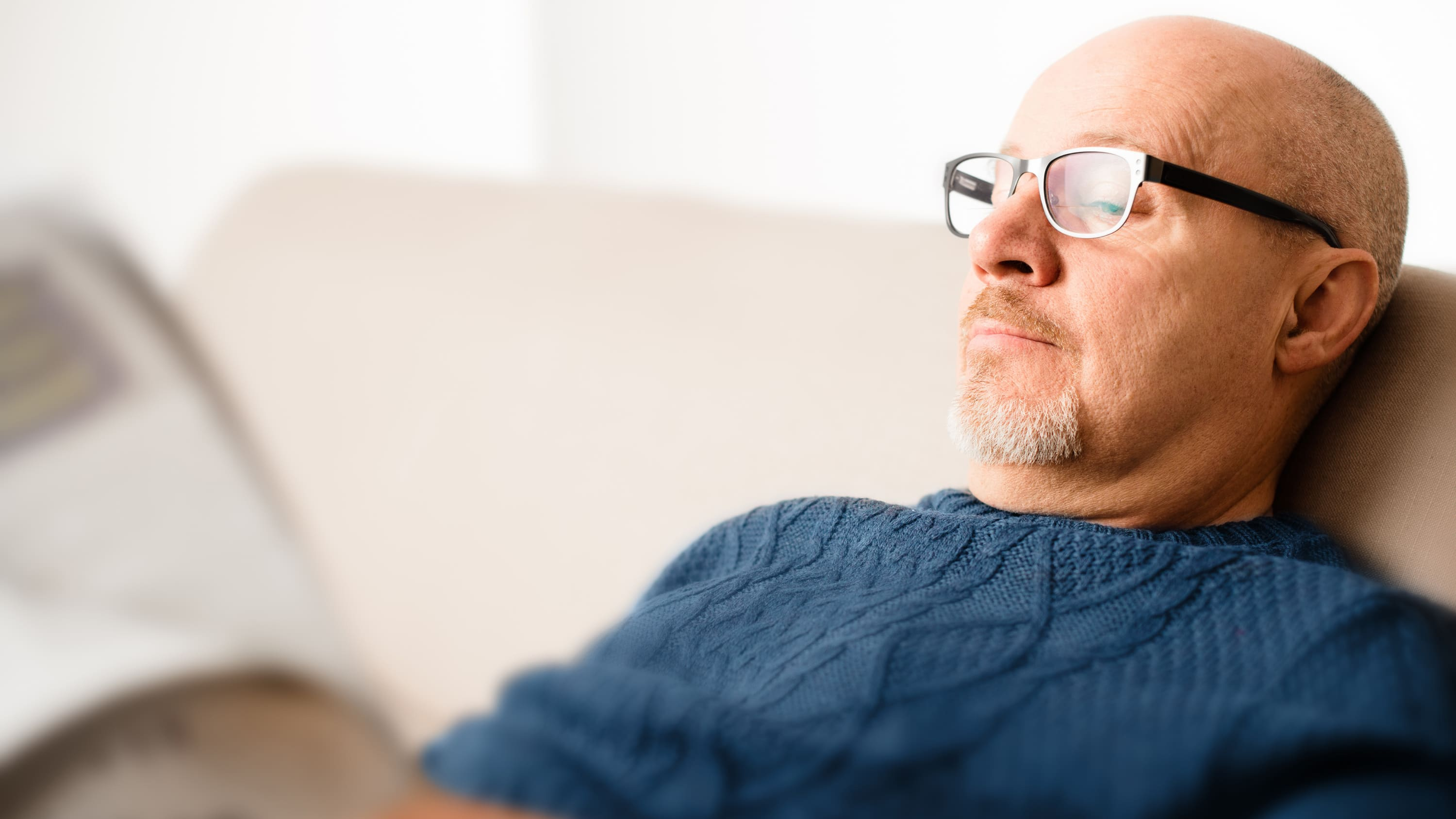 Middle-aged man who could be a candidate for peripheral vascular disease sits on the couch reading a newspaper.