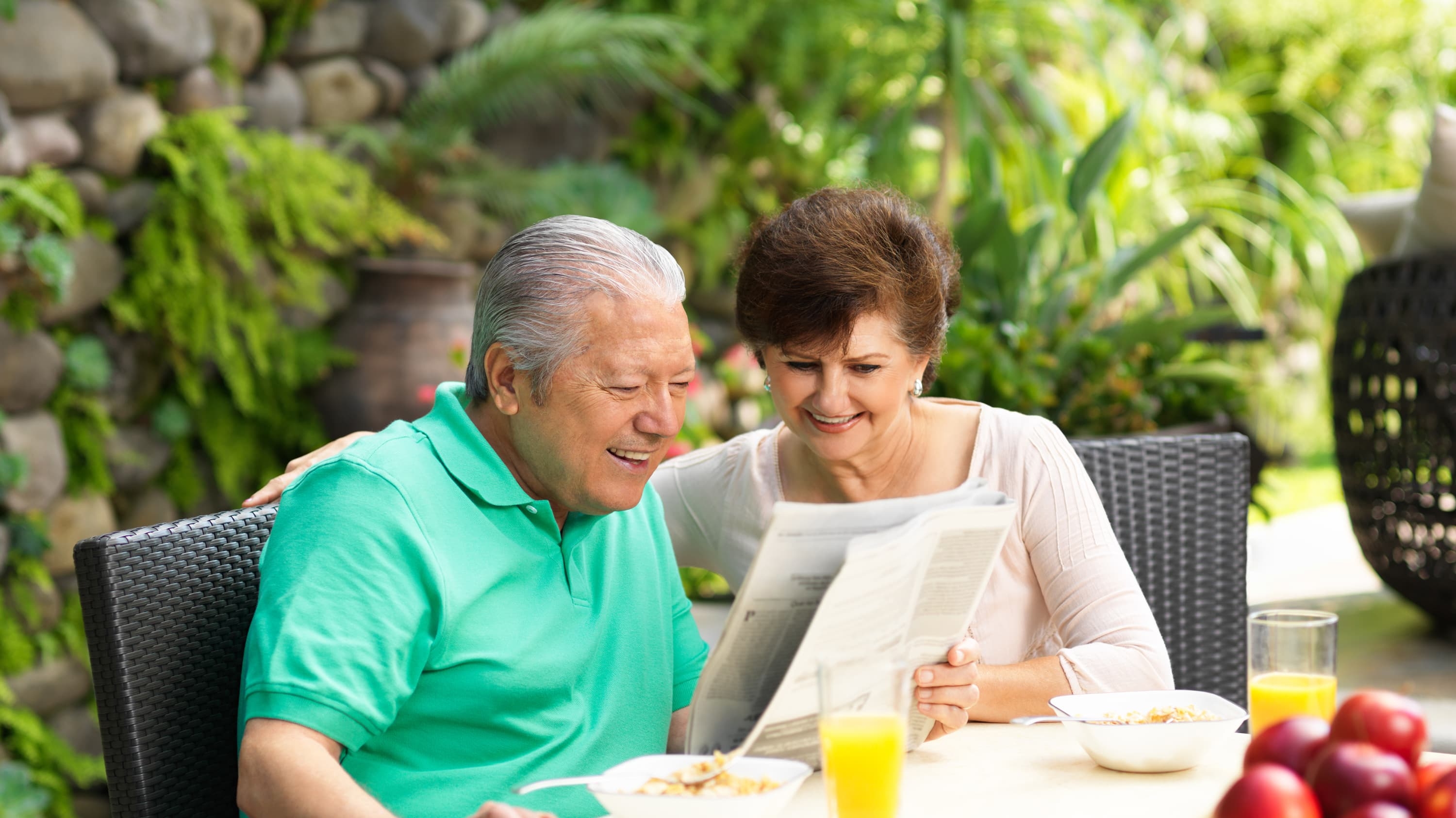 Senior couple reading newspaper while eating breakfast. Telomere research may uncover the secrets to living longer.