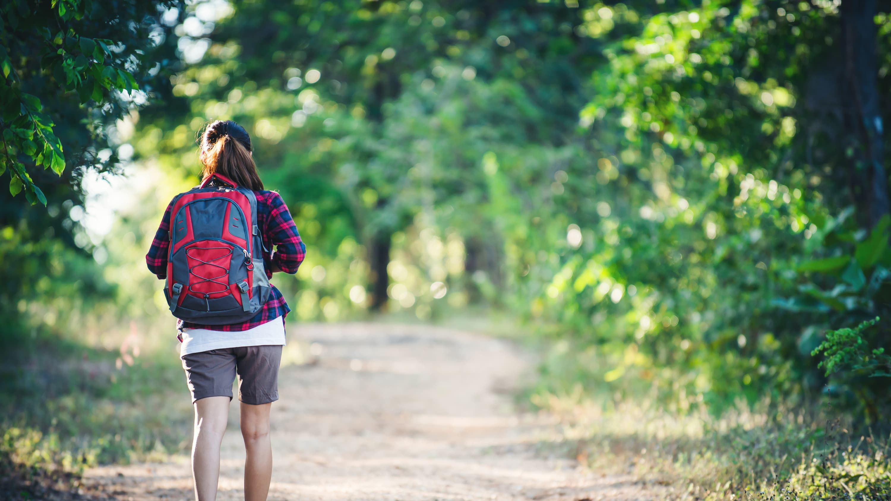 A woman with a backpack on hiking through the woods. She possibly recovered from sacroiliac joint fusion.