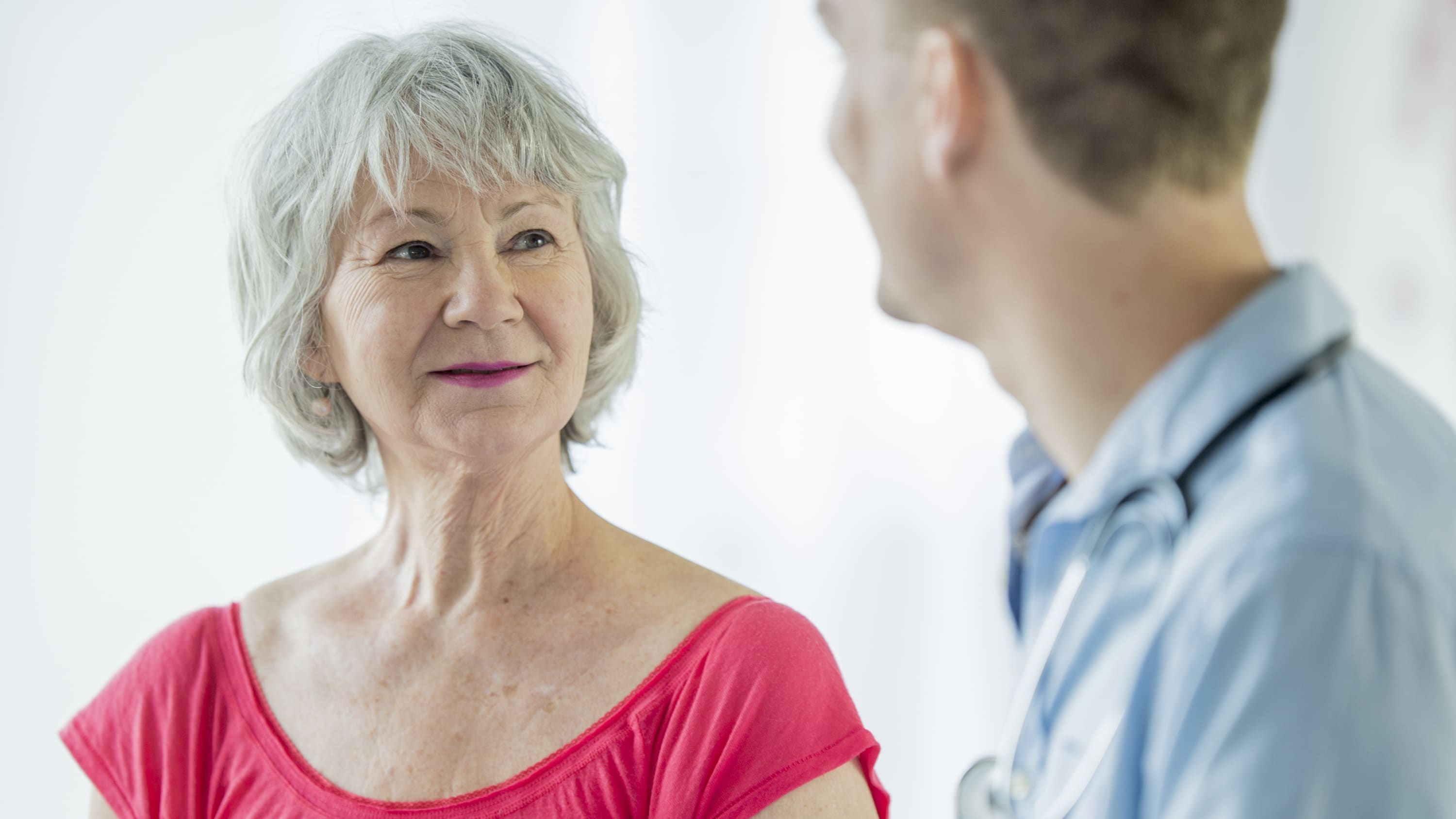 An older woman discusses the need for a tracheostomy with her doctor.