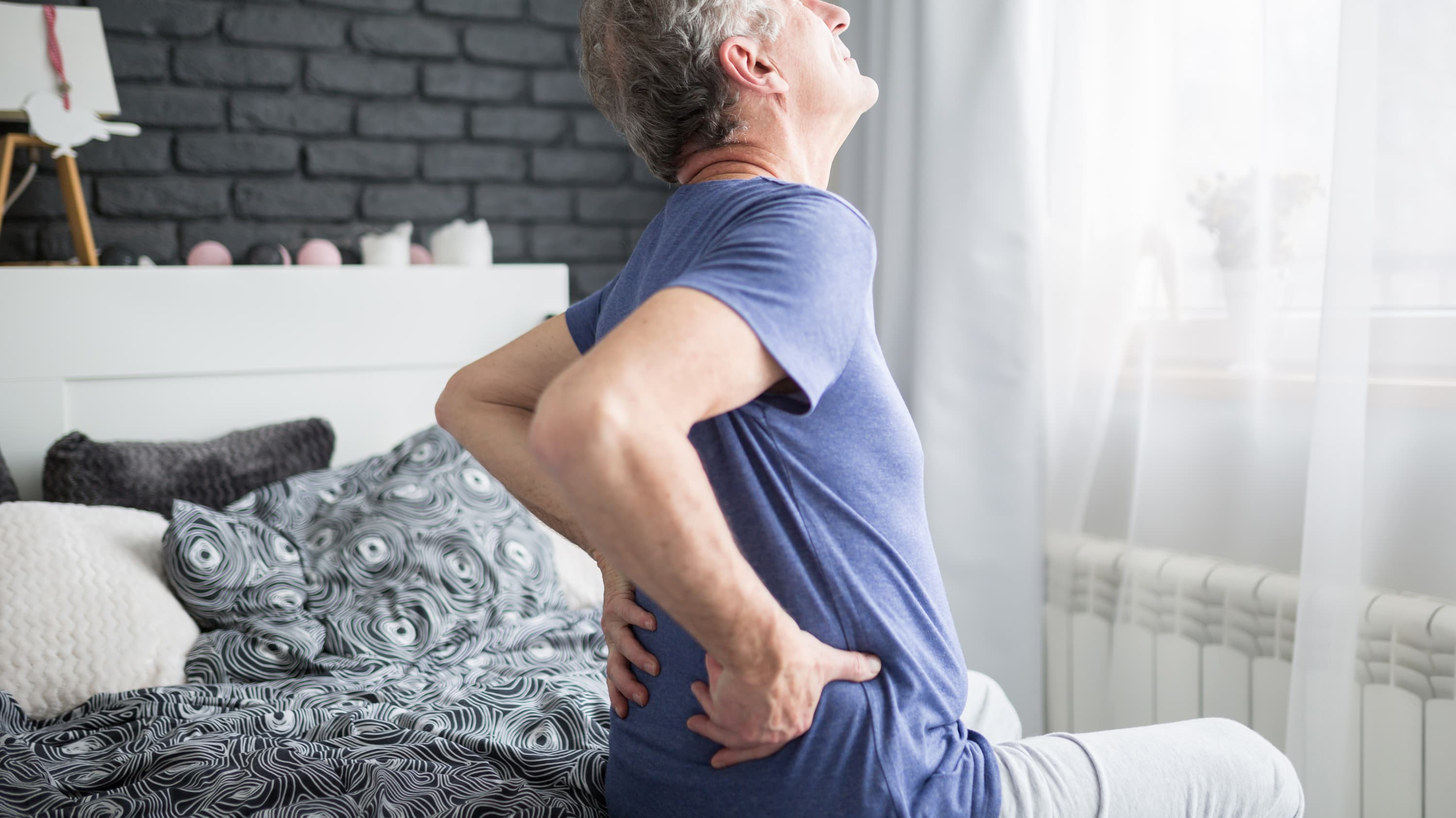 A man suffering from glomerulonephritis grabs his lower back in pain.