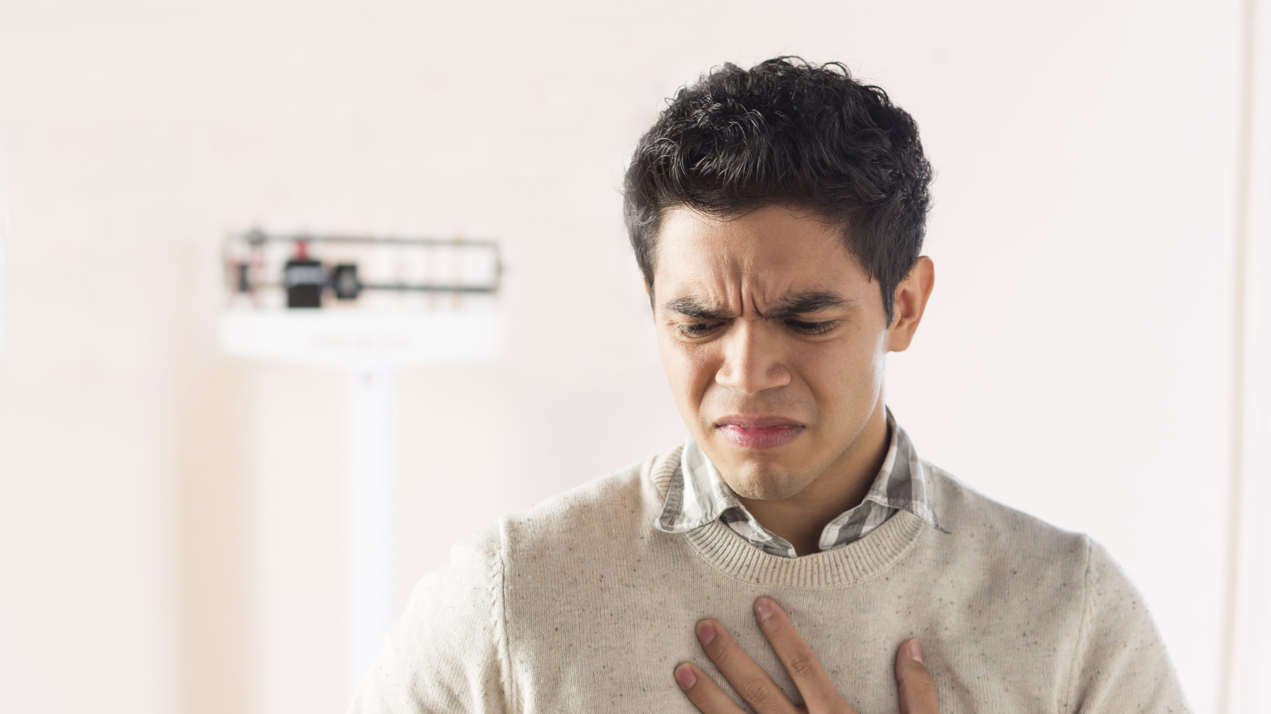 A young man experiencing dysphagia stands in an exam room holding his chest.