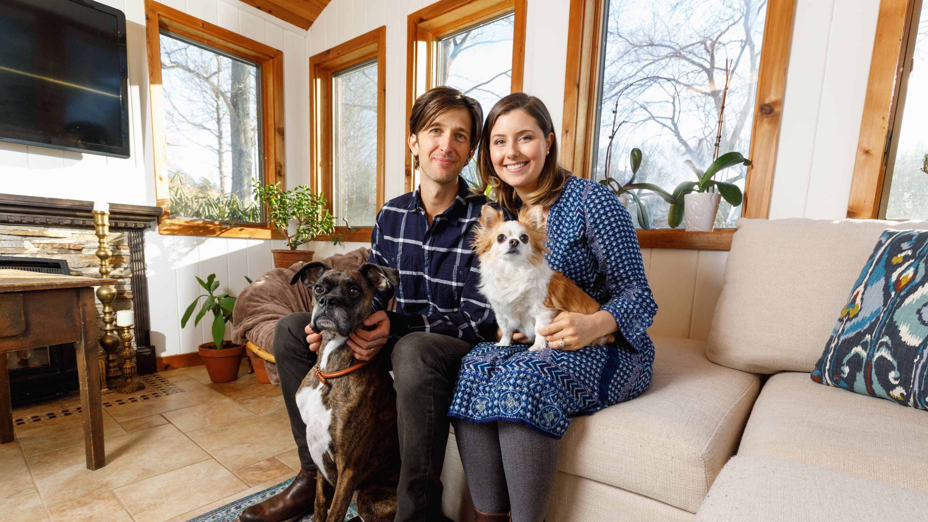 Marcus and Laura Gordon with their two dogs on the couch