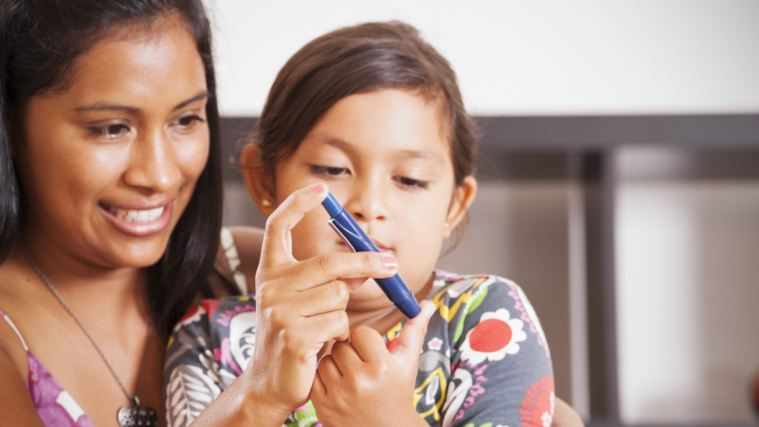 A mother helps her young daughter use a device to test blood sugar in people with diabetes