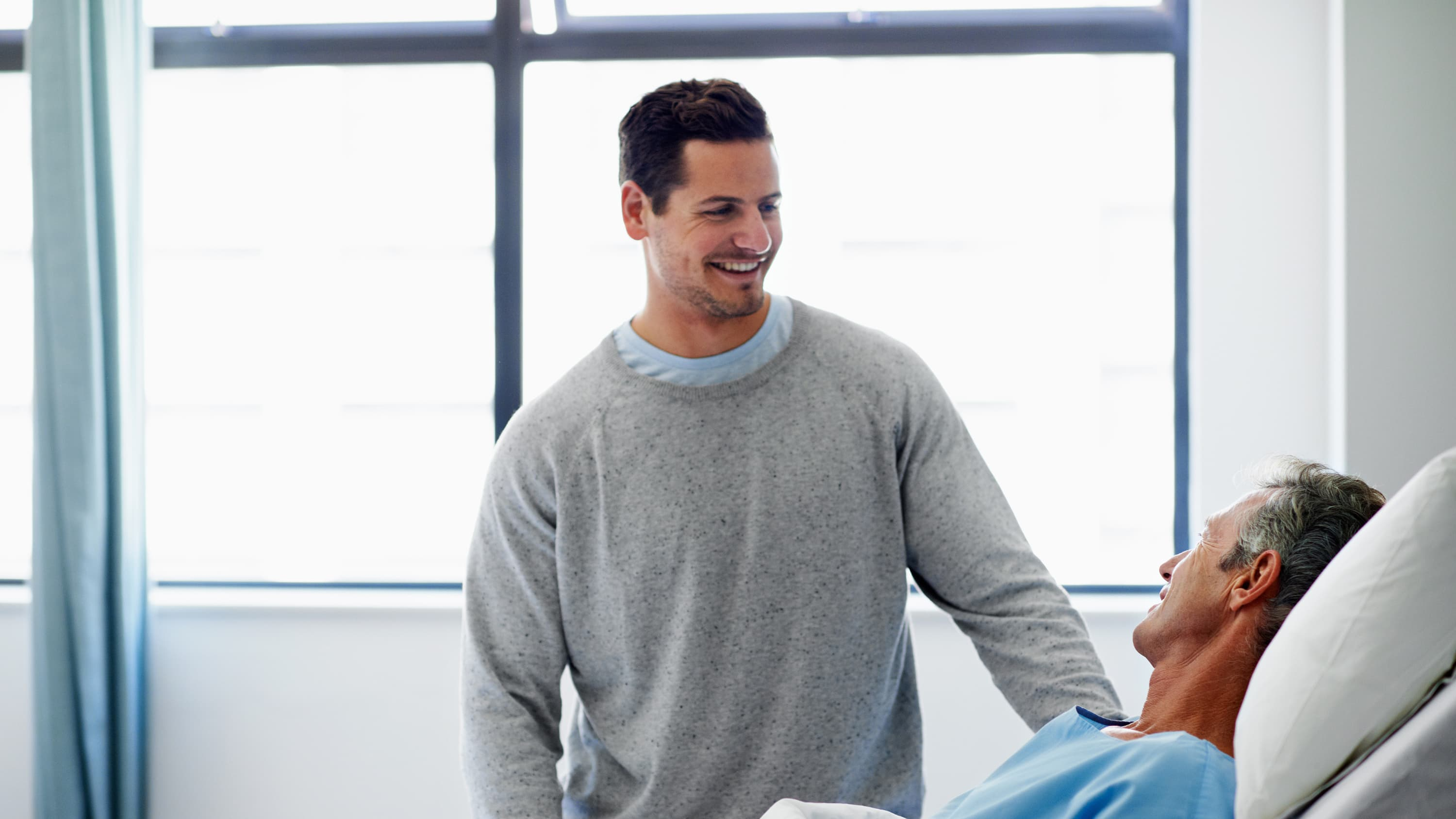 A visitor stands smiling at a patient's bedside after successful minimally invasive thoracic surgery