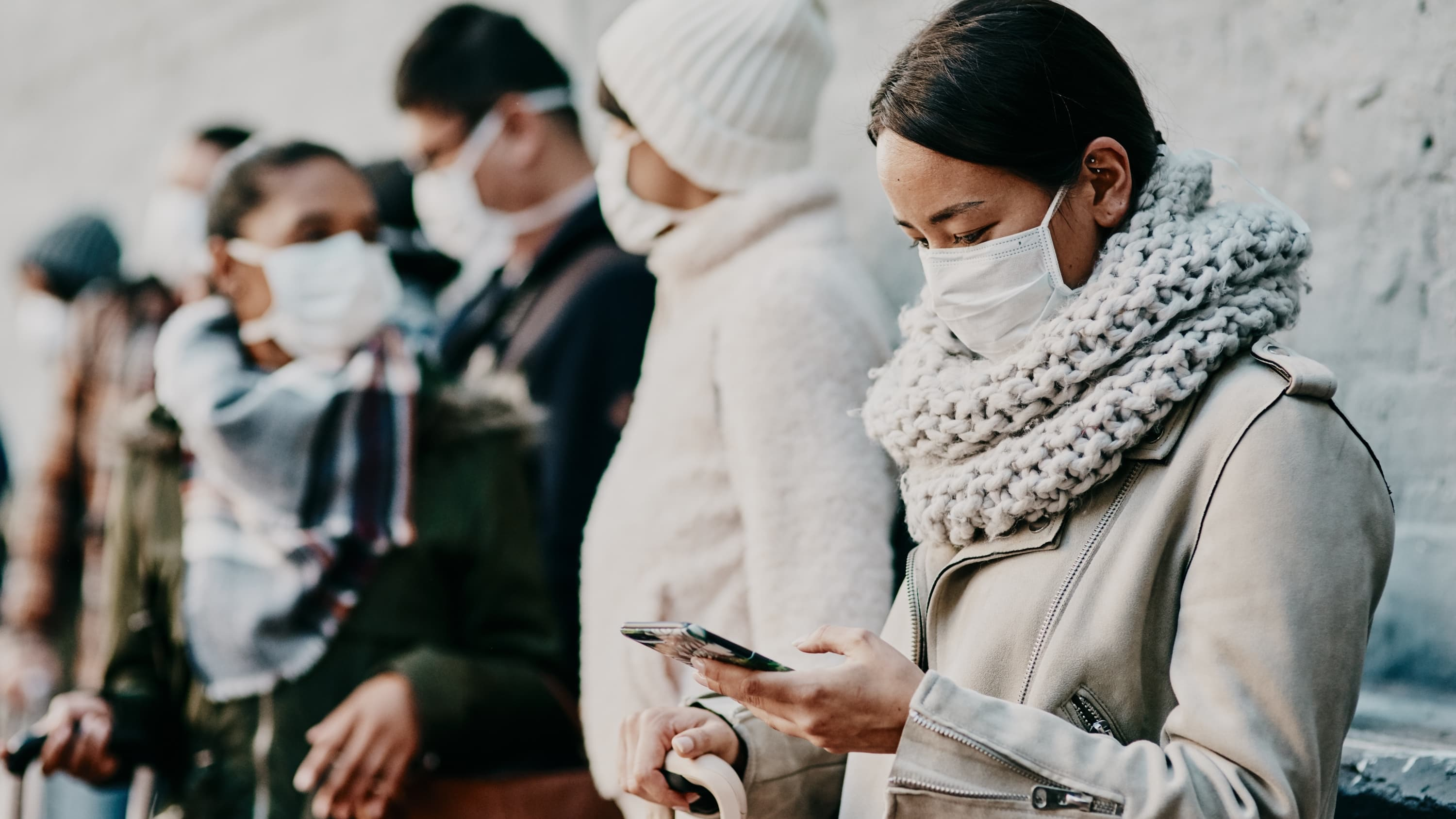 woman in a mask waiting on line while reading her phone, possibly learning of SalivaDirect, the new COVID-19 saliva tes