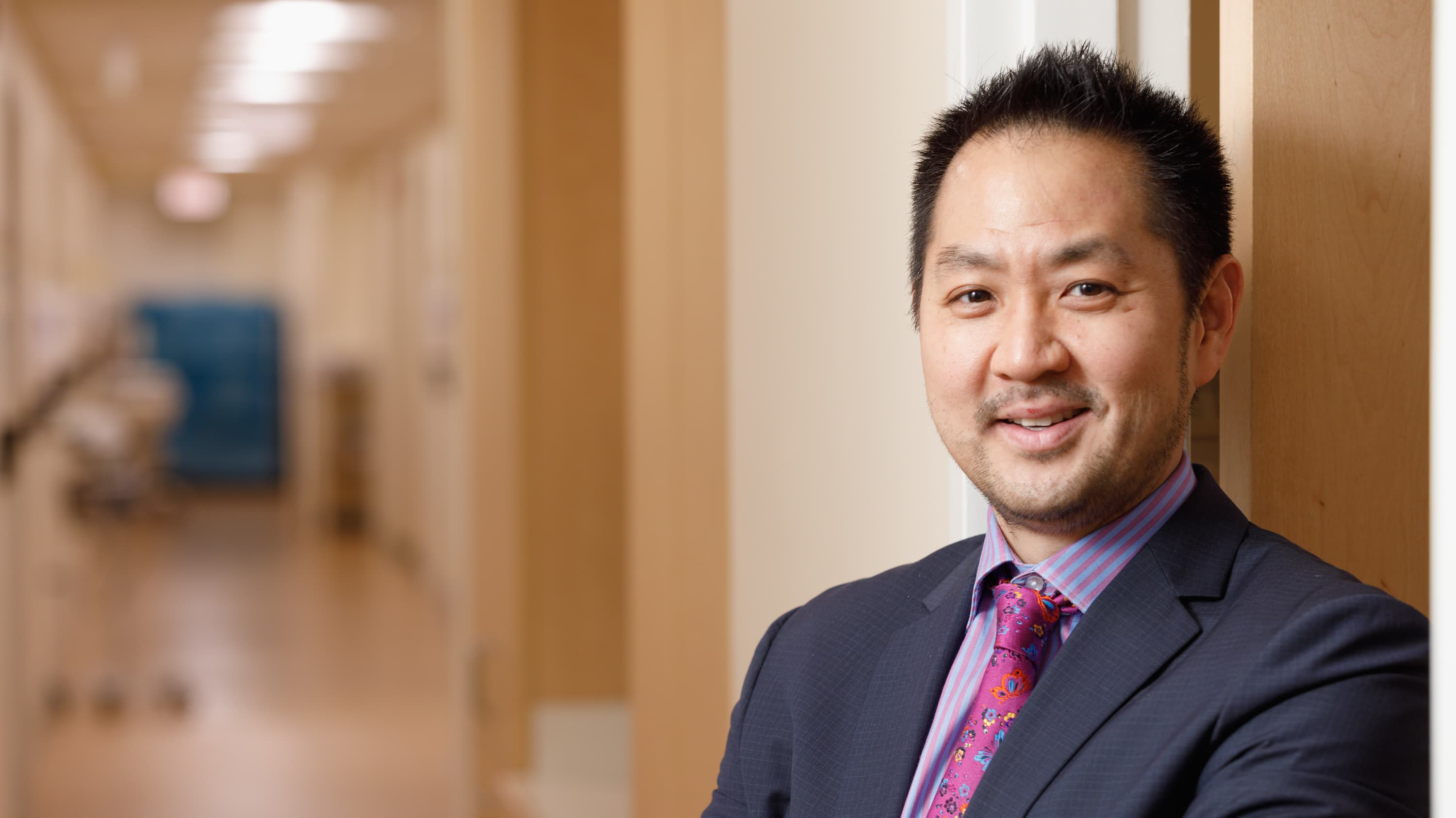Portrait of Dr. Peter Whang in the hallway. He is wearing a purple dress shirt, tie and jacket.