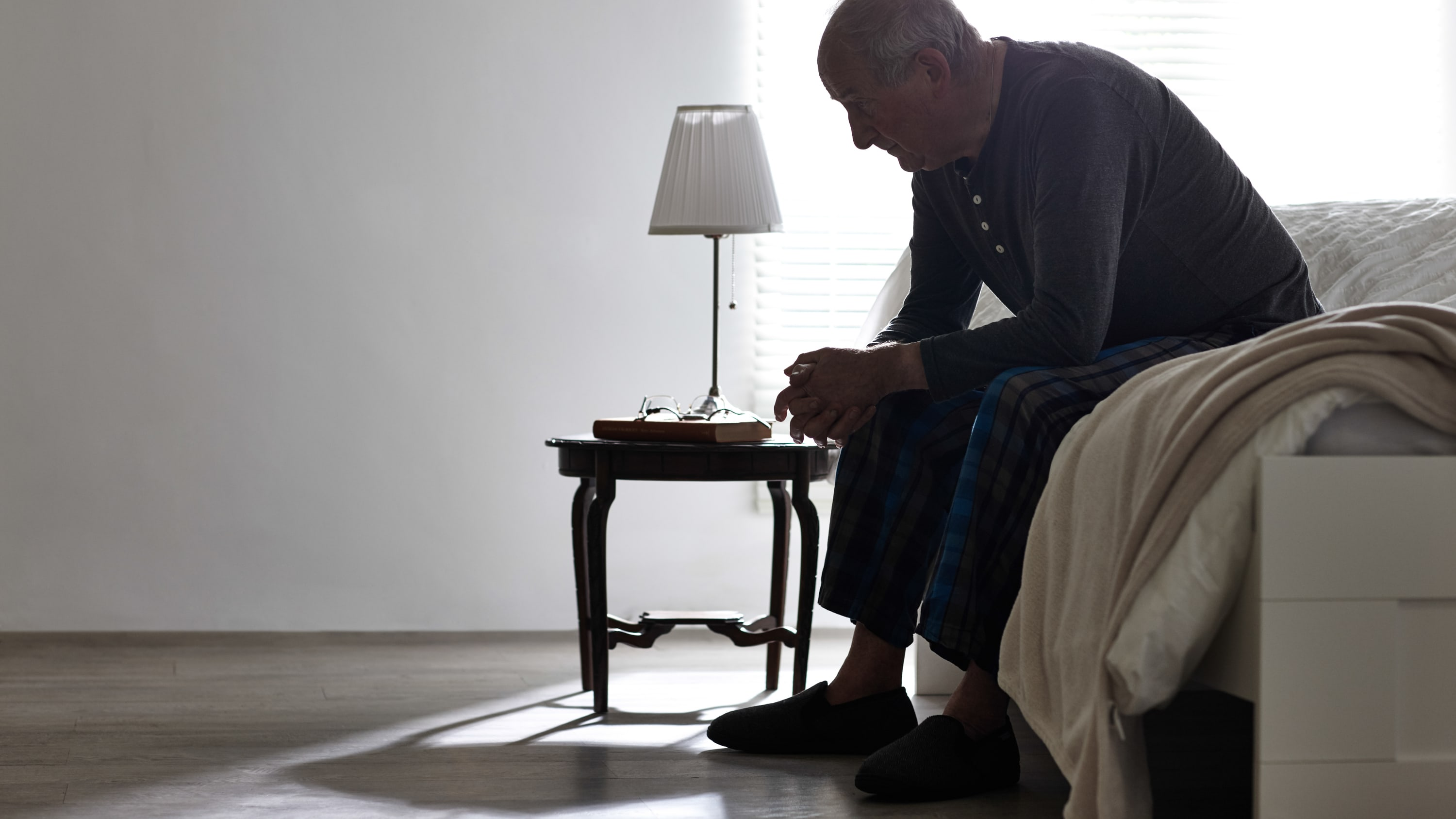 An older man with congestive heart failure sits on the edge of his bed feeling exhausted.