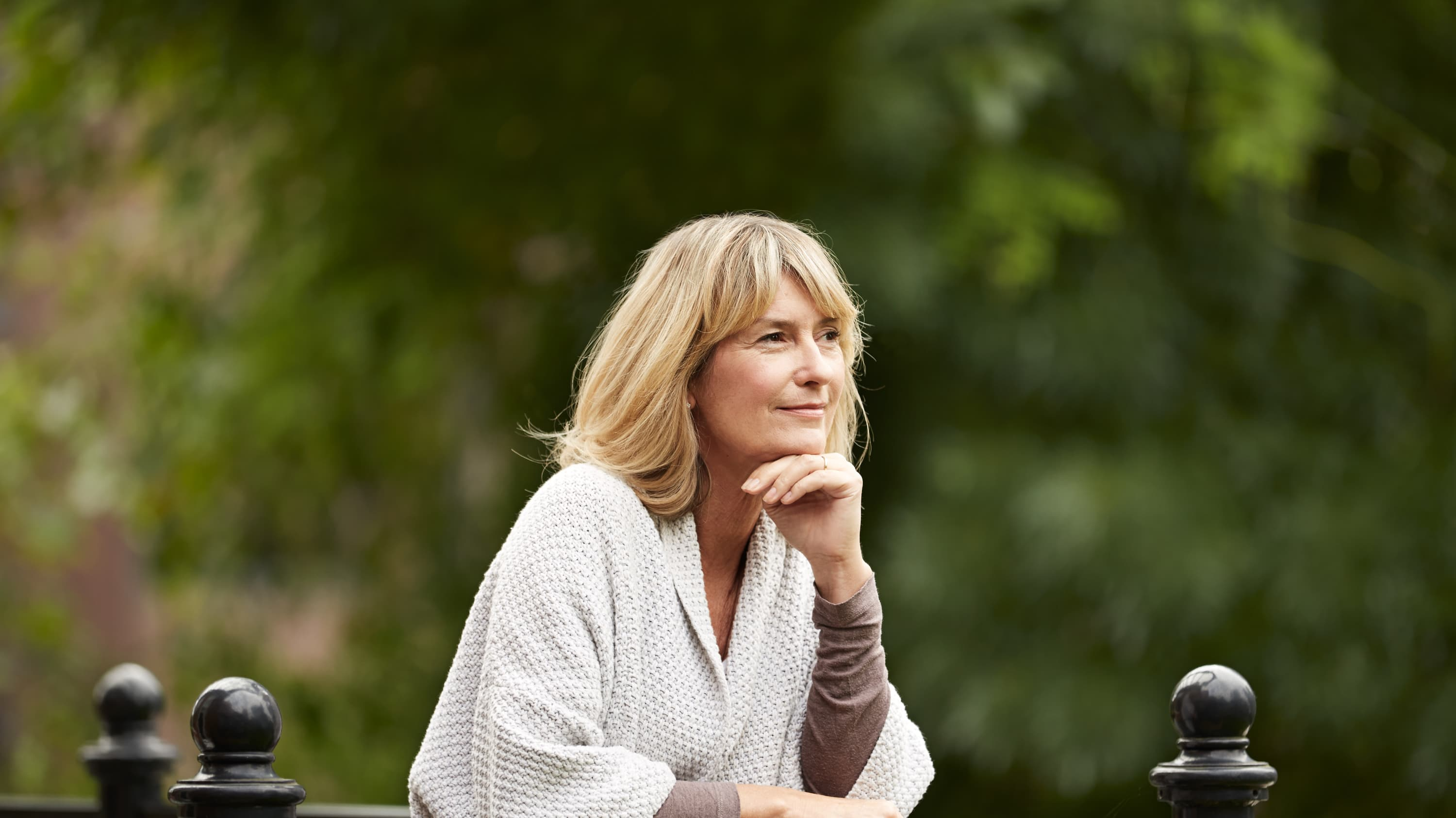 A middle-aged woman gazes out above her balcony, deep in thought, possibly about low bone density