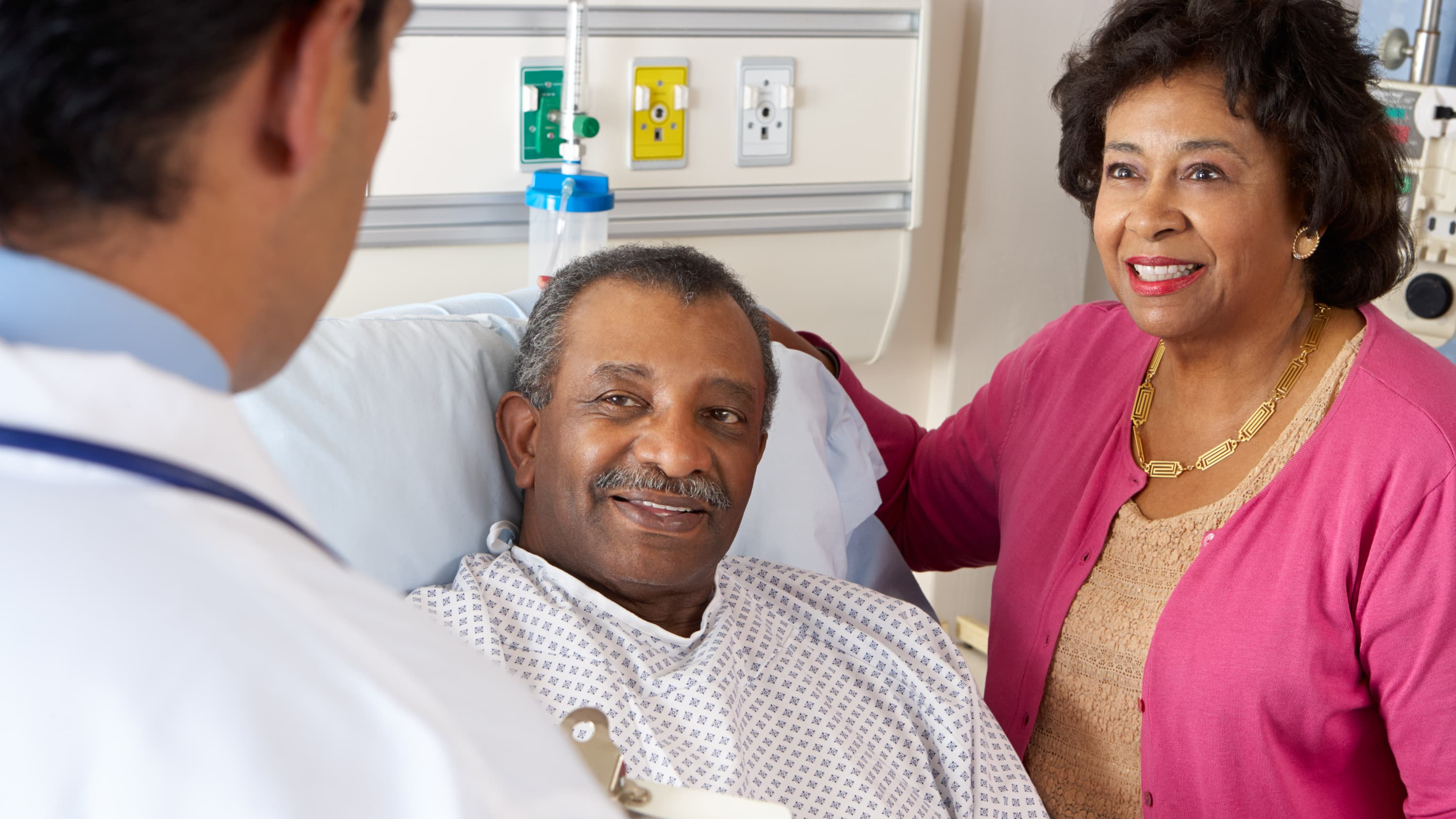 A man in a hospital bed talks to his wife (in a bright pink sweater) and his doctor after minimally invasive gastrointestinal surgery.