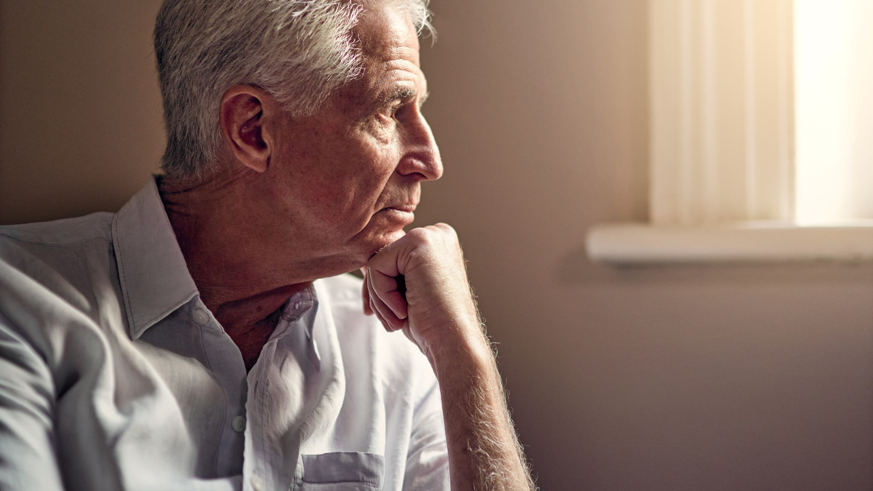 An elderly gentlemen looks out a window, who may be worried about pancreatic cancer.