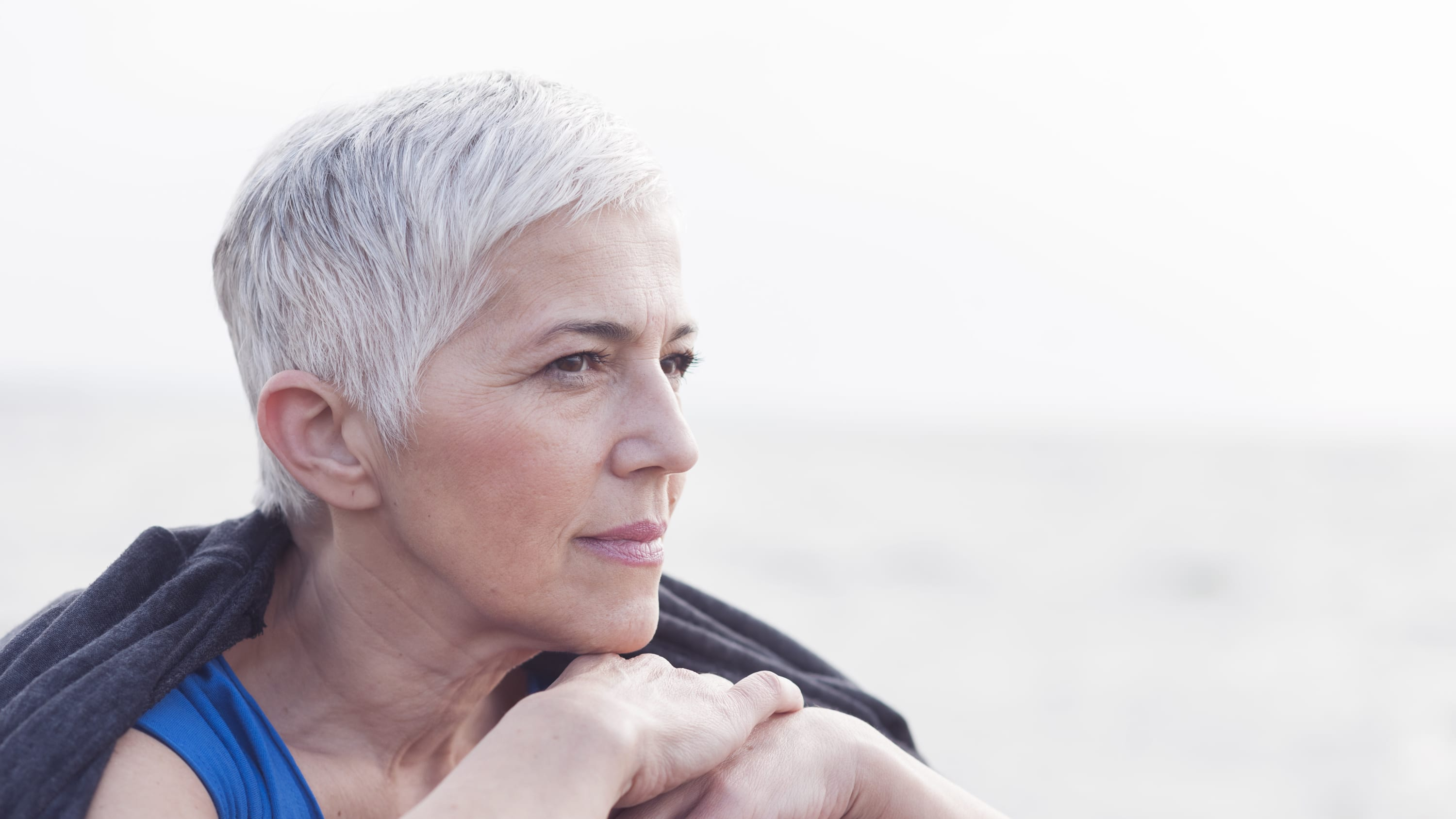 a woman with gray hair looks out at the water from a boat. she possibly has uveitis