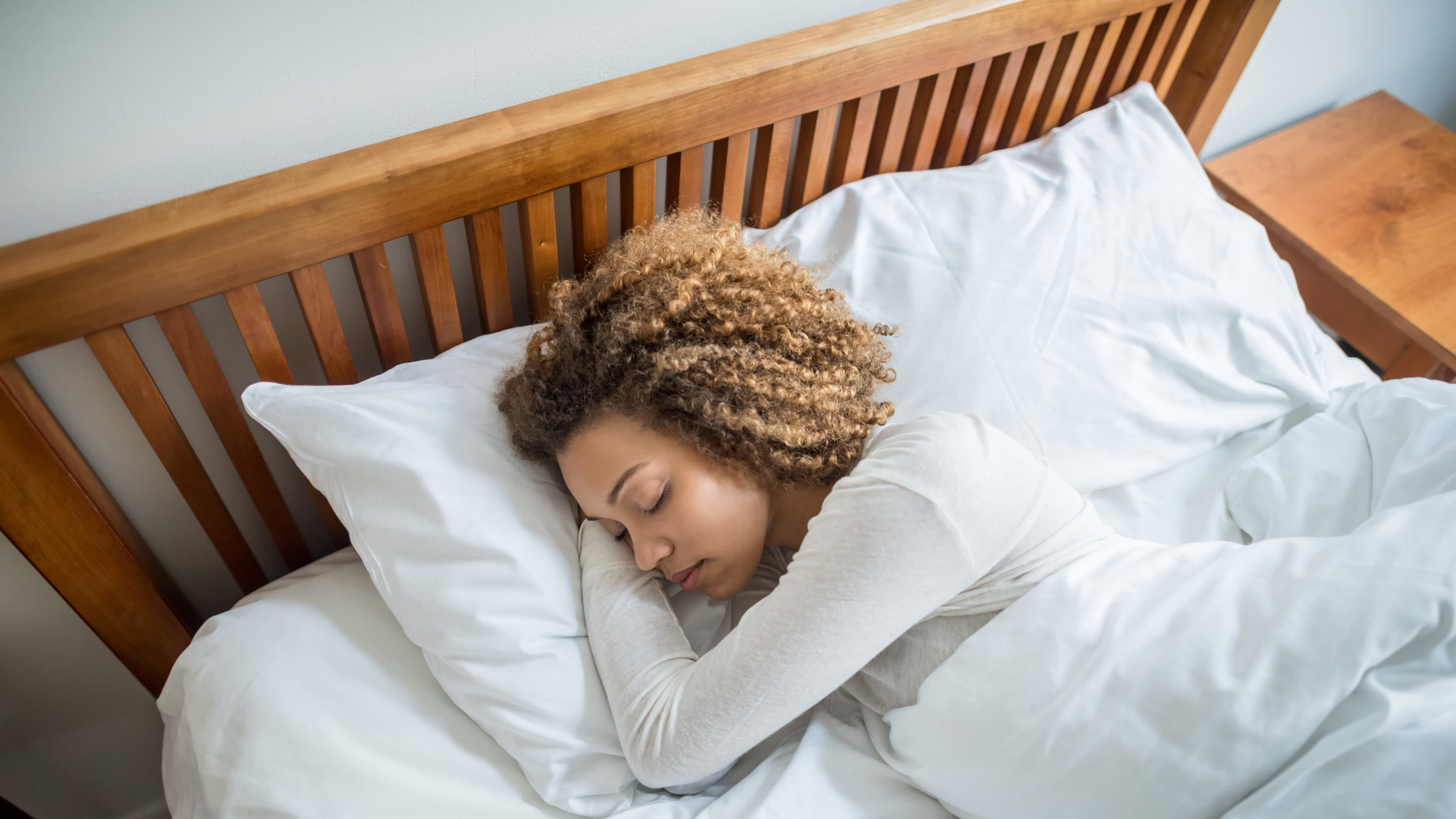 An African American woman enjoys a restful sleep in bed after being diagnosed in a sleep study and then treated.