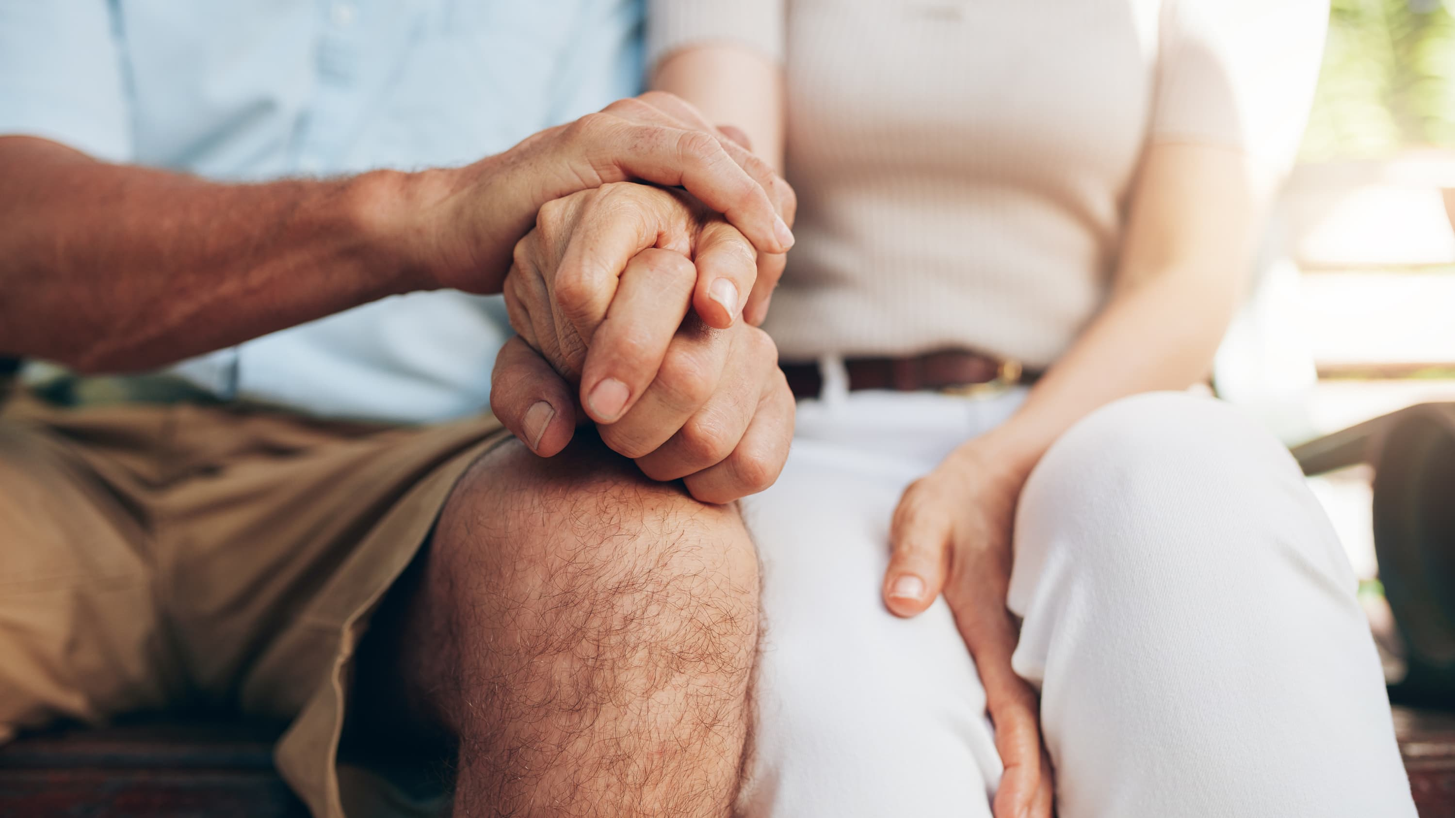 Husband holds his wife's hand after diagnosis of coronary artery disease