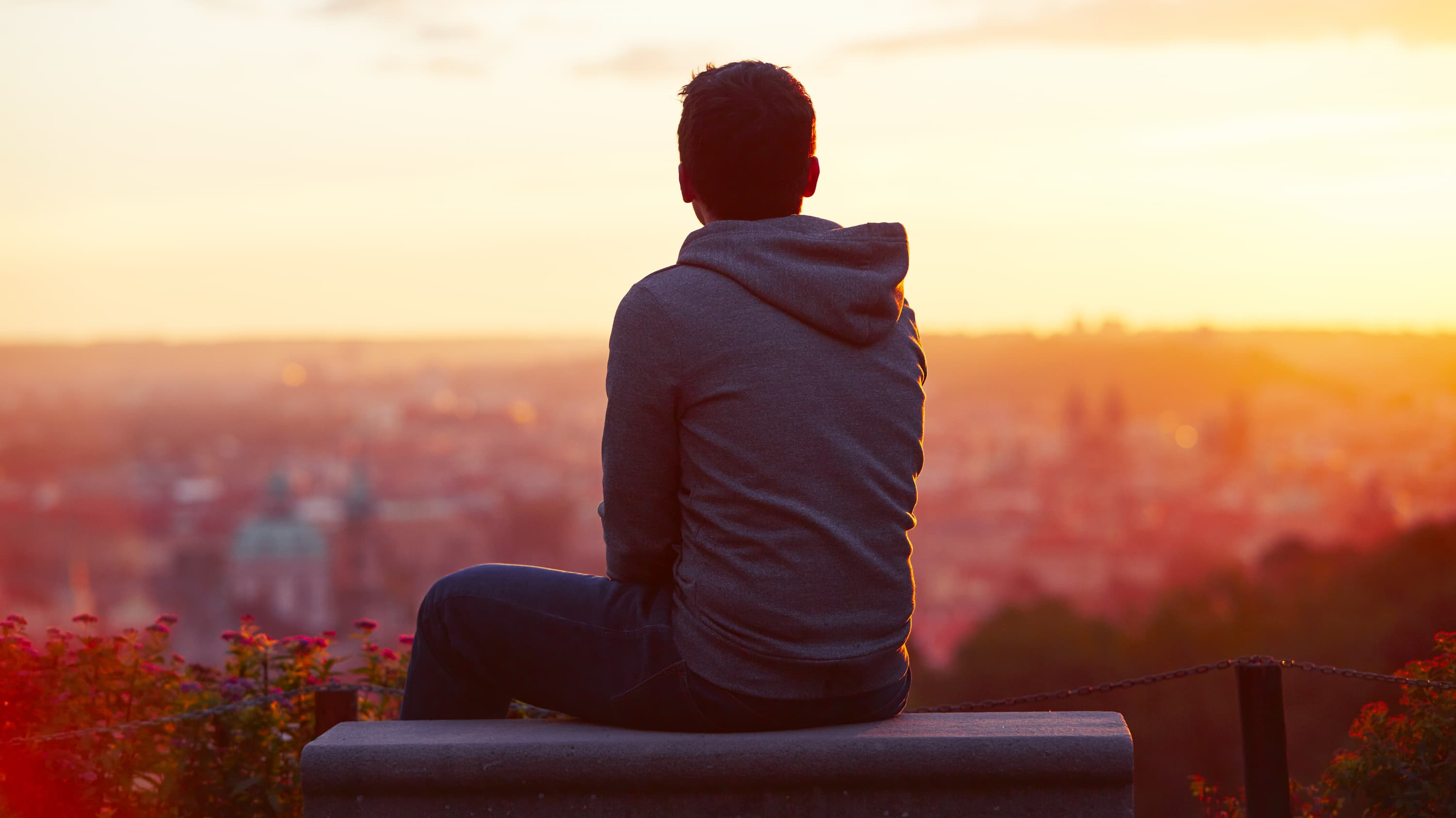 young man sitting on a bench looking out over a city, worried and stress about COVID-19