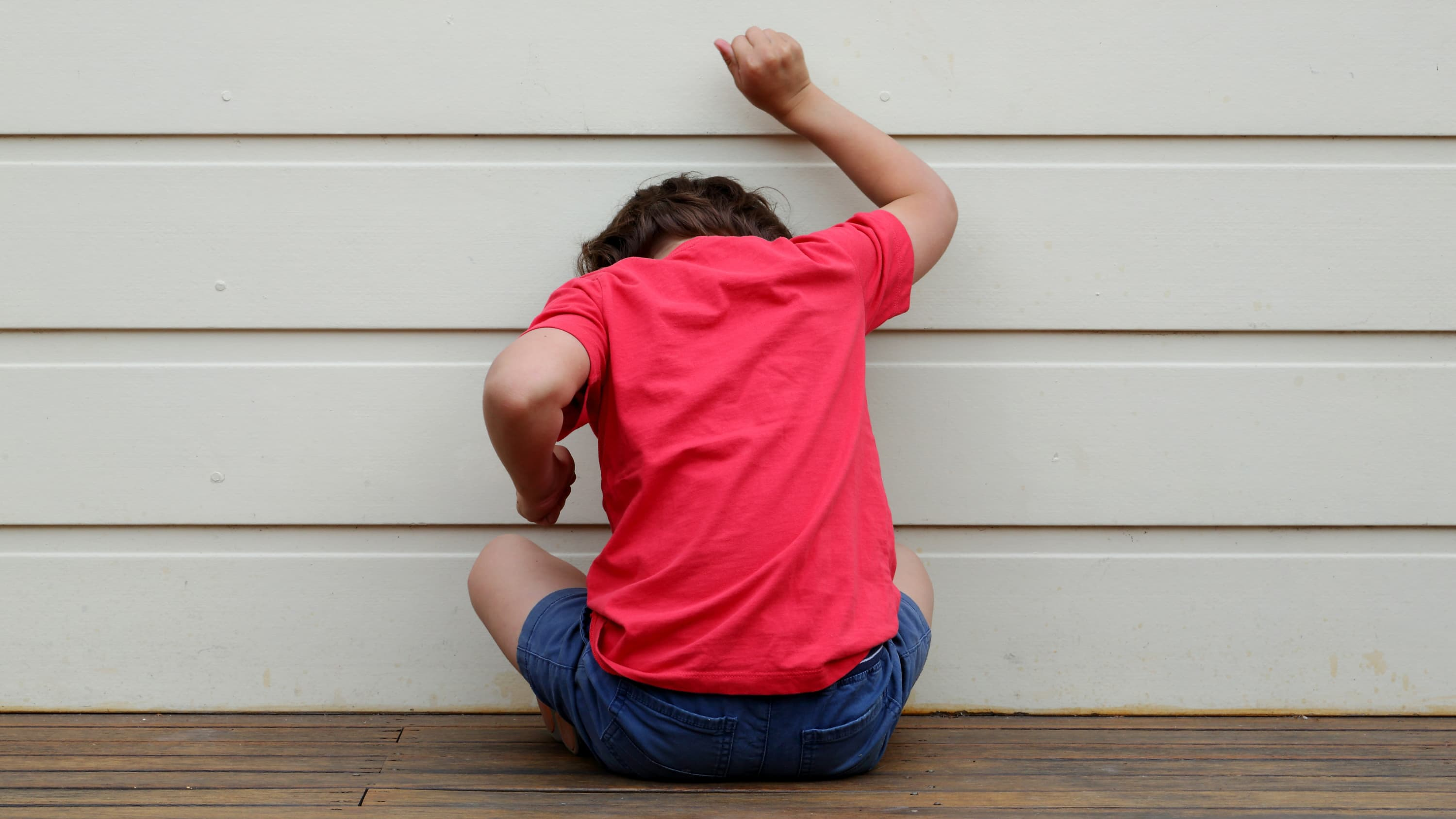 A child in a pink shirt who may have oppositional defiant disorder bangs on a wall.
