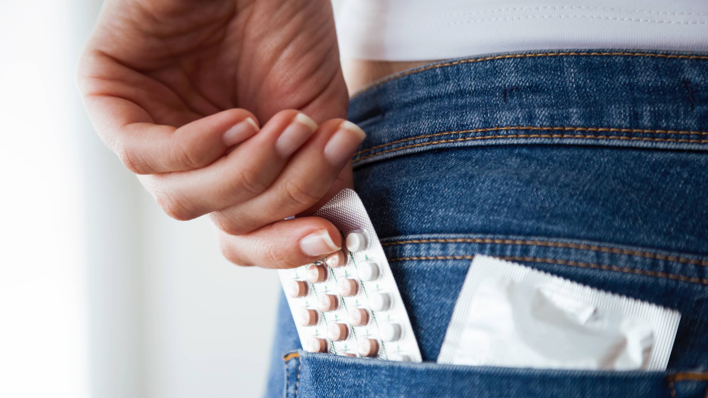 Woman with contraceptive pills and condom in the pocket of blue jeans