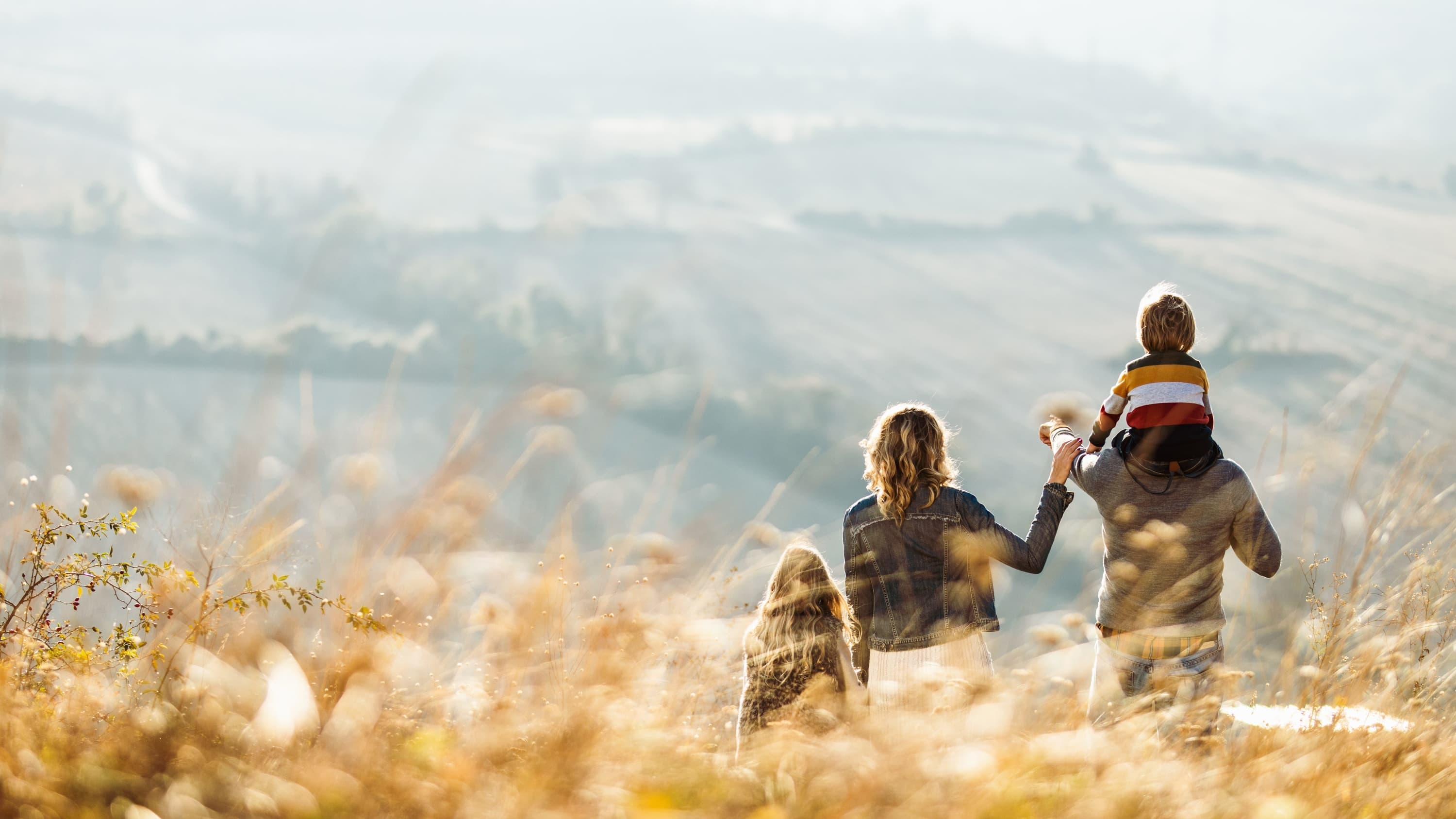 Rear view of a family standing on a hill in autumn day, symbolizing hope for the end of the COVID-19 pandemic