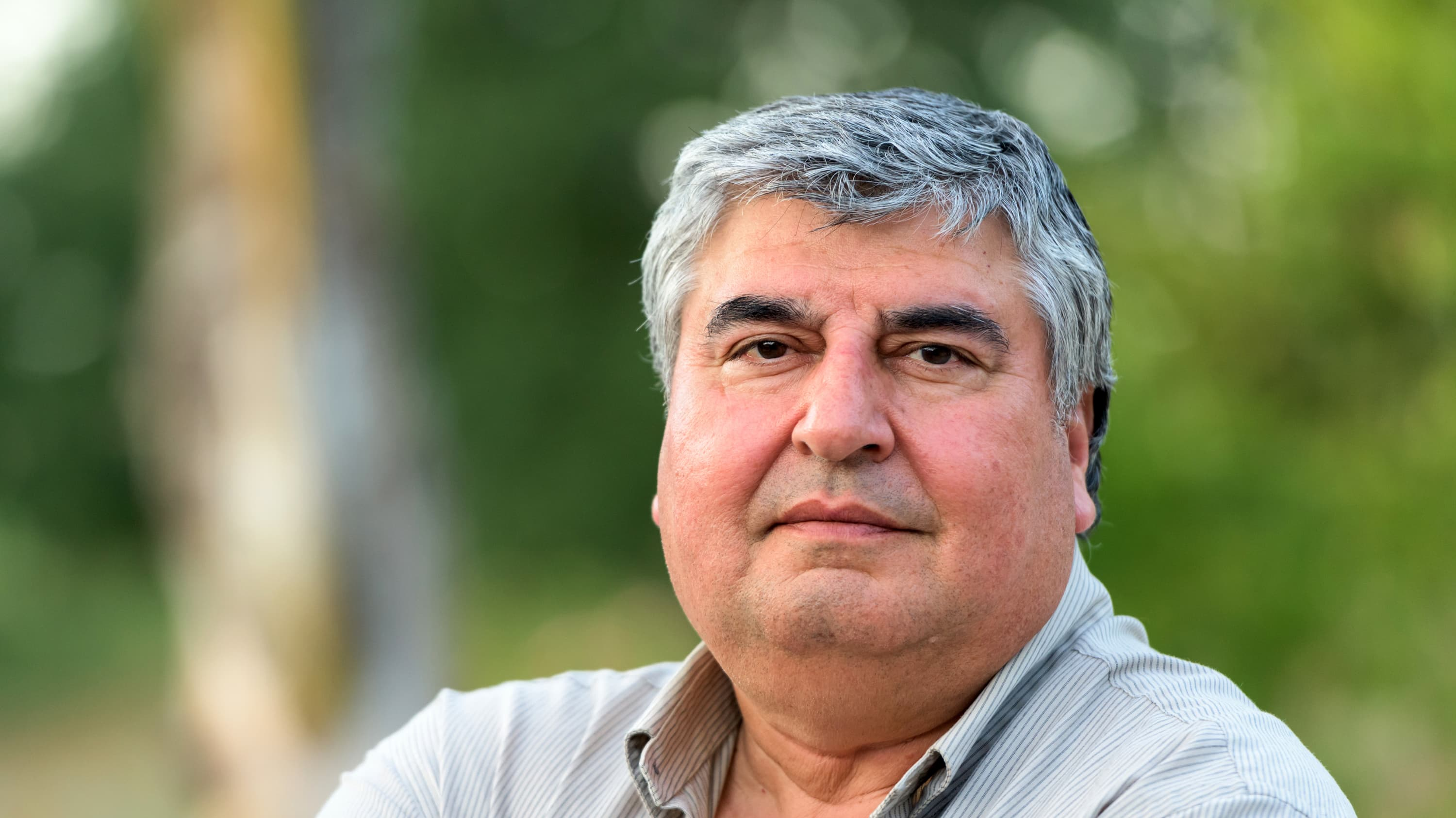 An overweight man who may have peripheral artery disease looks into the camera. He is wearing a grey polo shirt against a green, leafy background.