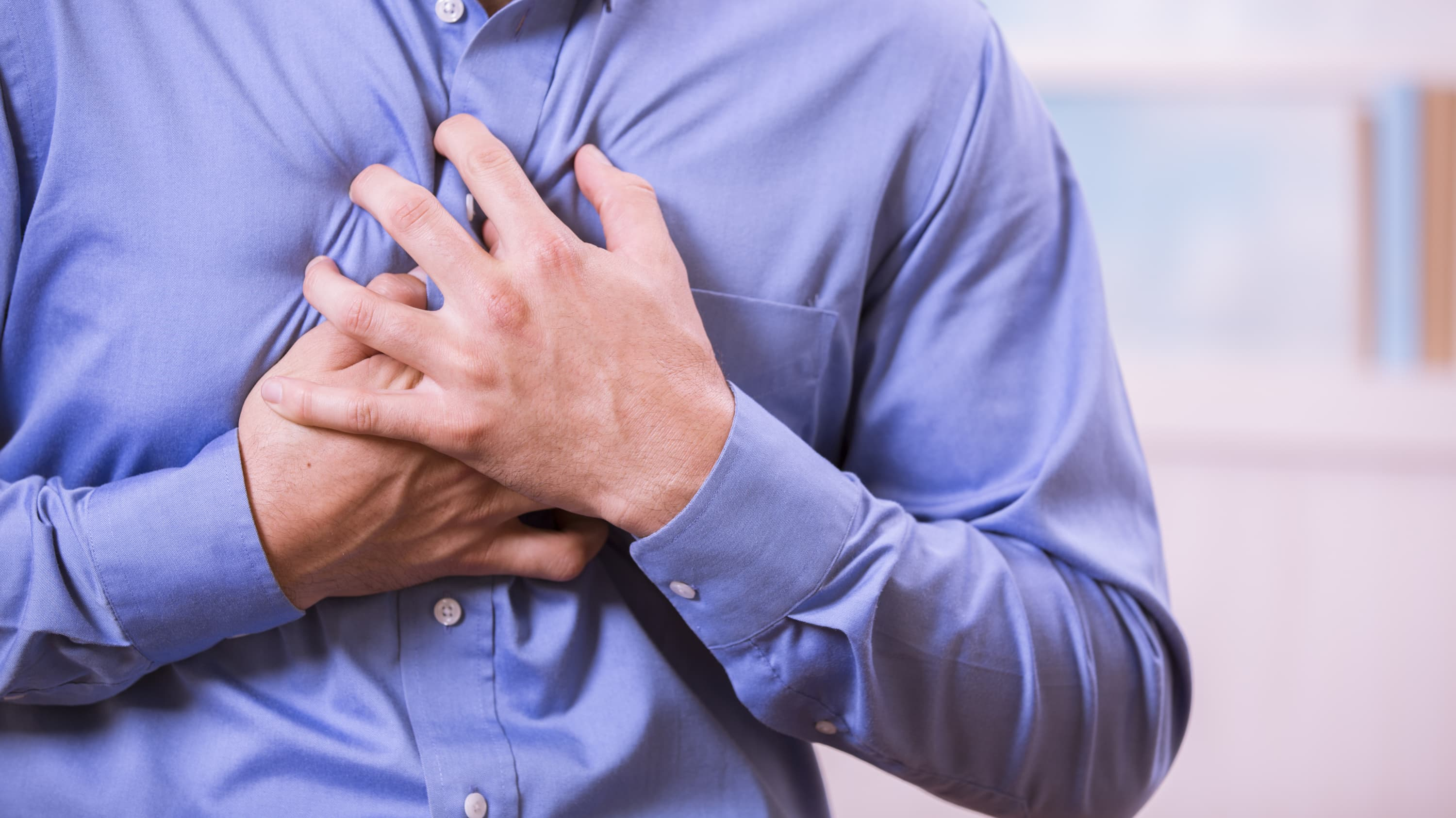 A man in a blue shirt who may have a pulmonary embolism clutches his chest.