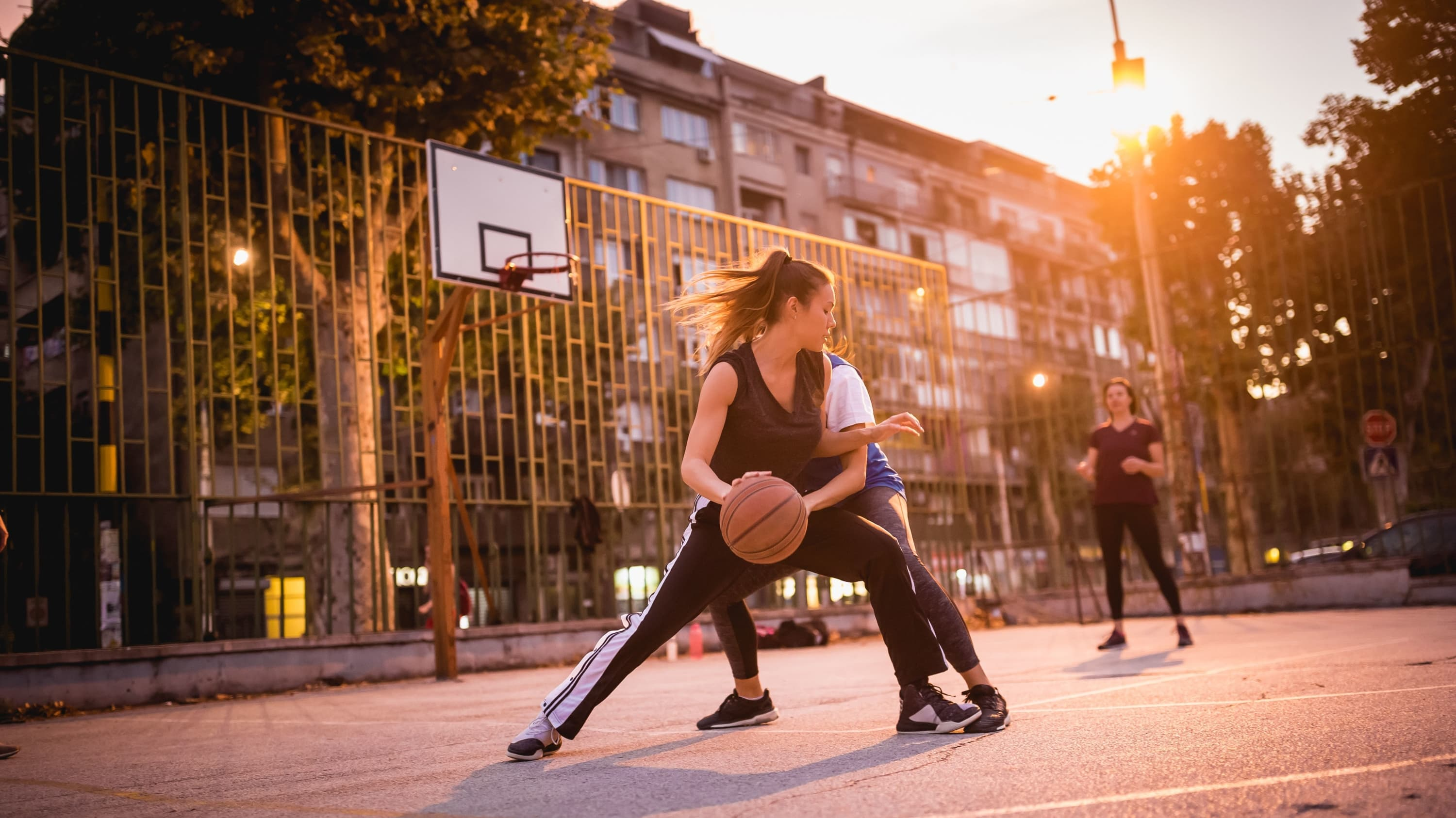 two women playing basketball outside, demonstrating how a meniscus tear—and need for meniscus transplantation—can occur