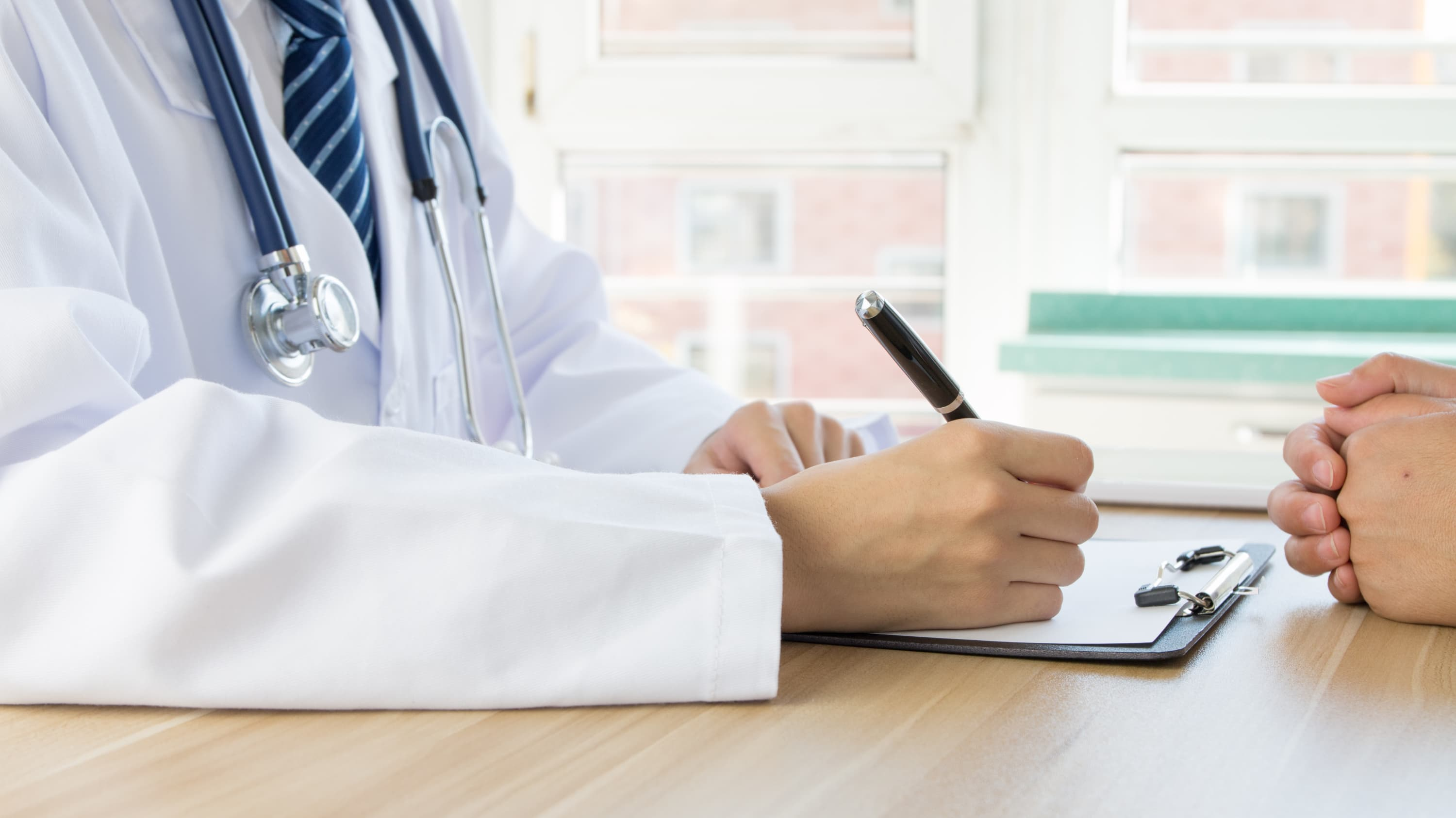 .A doctor writes notes for a patient, one possibly with Hepatitis B or C