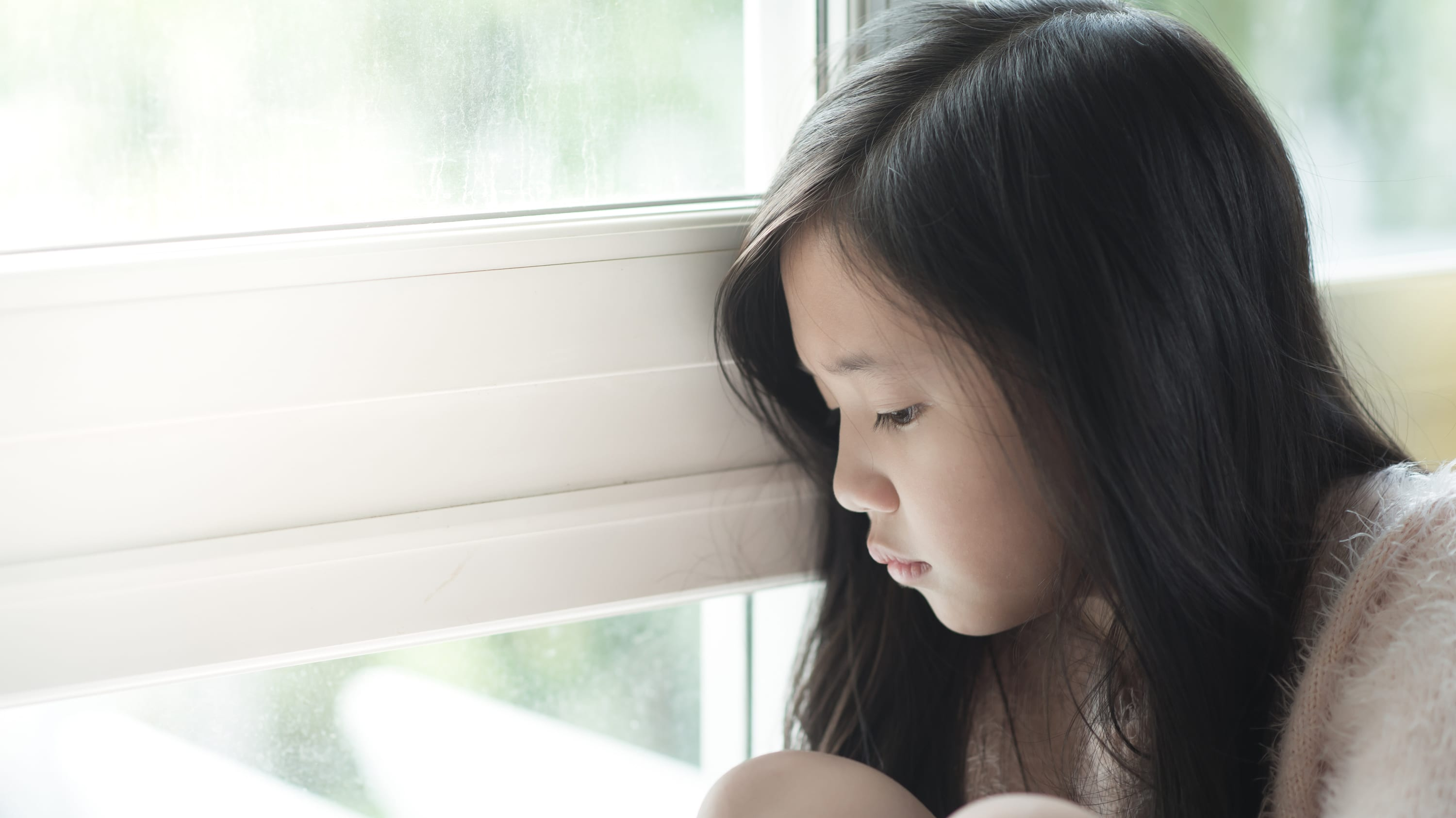 A child who may need a pediatric kidney transplant sits by a window