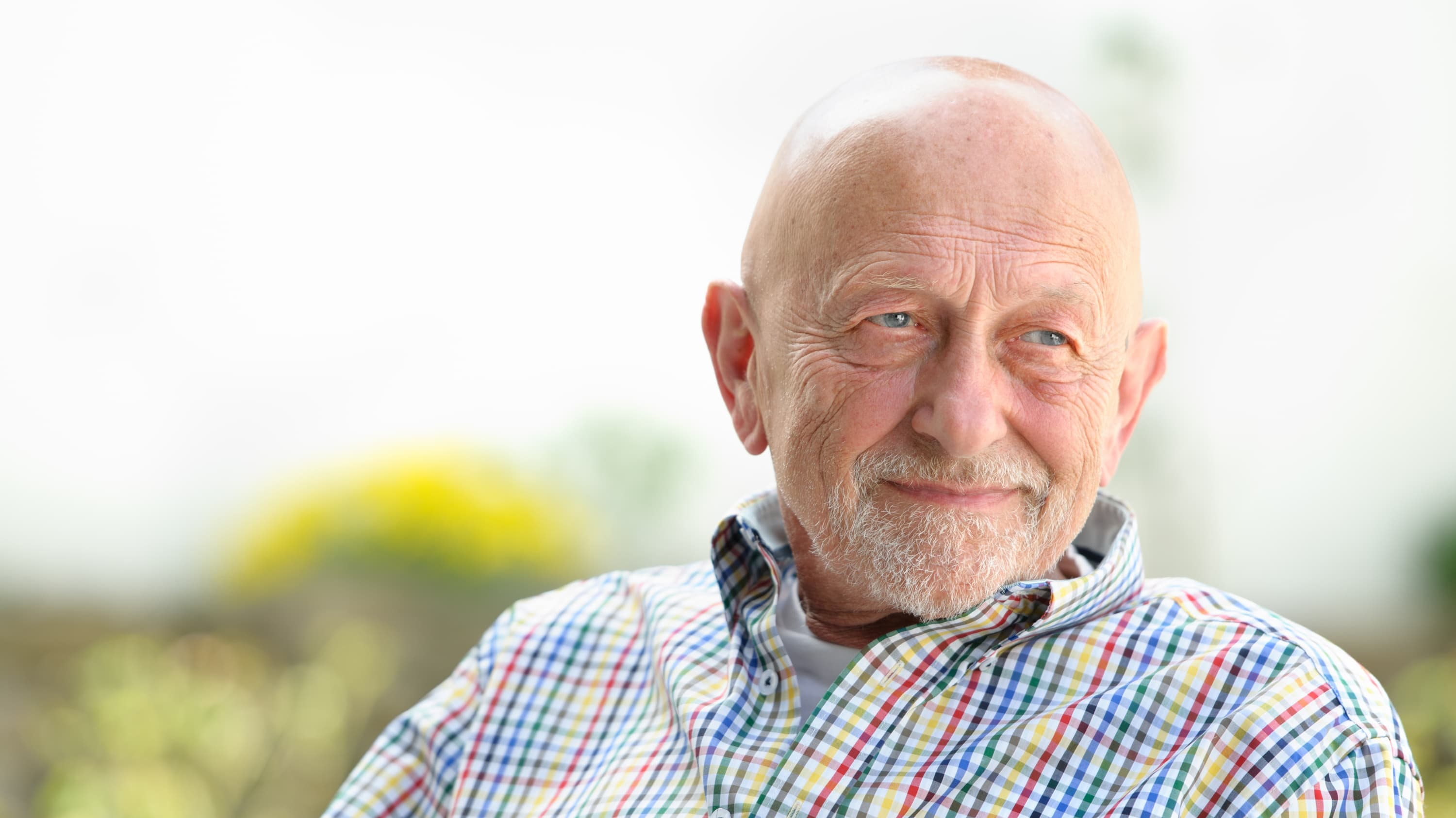 An older man who needs deep brain stimulation looks off in the distance.