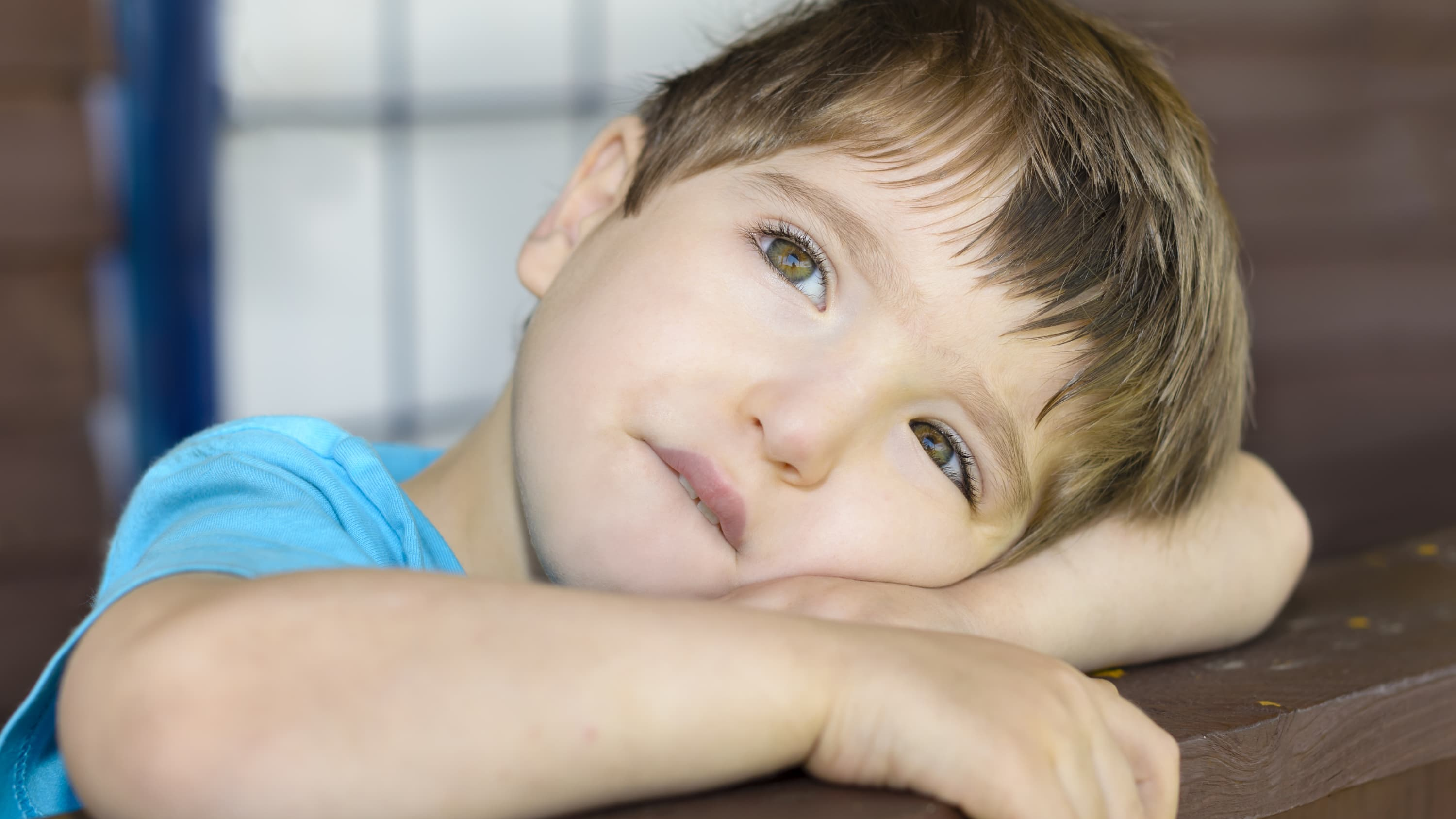 A child with a movement disorder looks off into the distance.