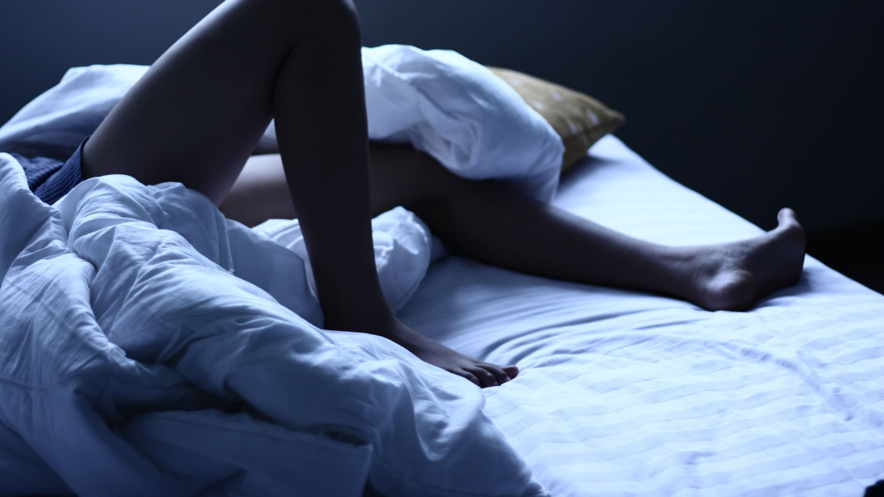 A person in bed with restless legs syndrome.