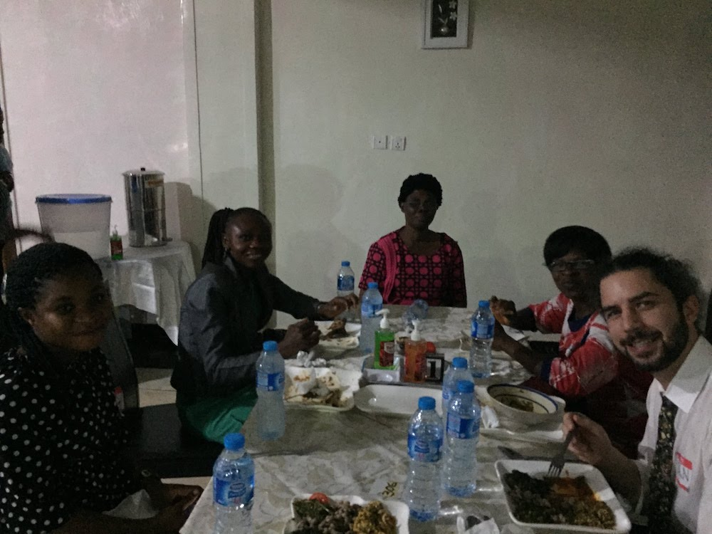 An instructor and participants in the HAPPINESS Project training session sit at a table and socialize over a meal.