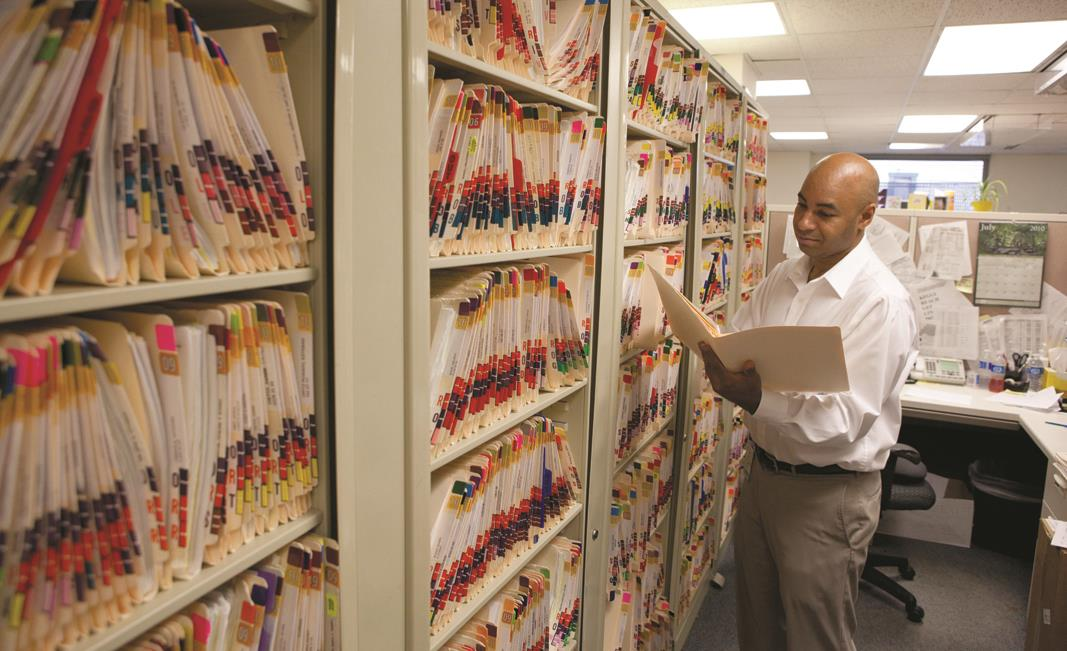 Trevor Lewis, a senior administrative assistant in orthopaedics, looked over patient records
