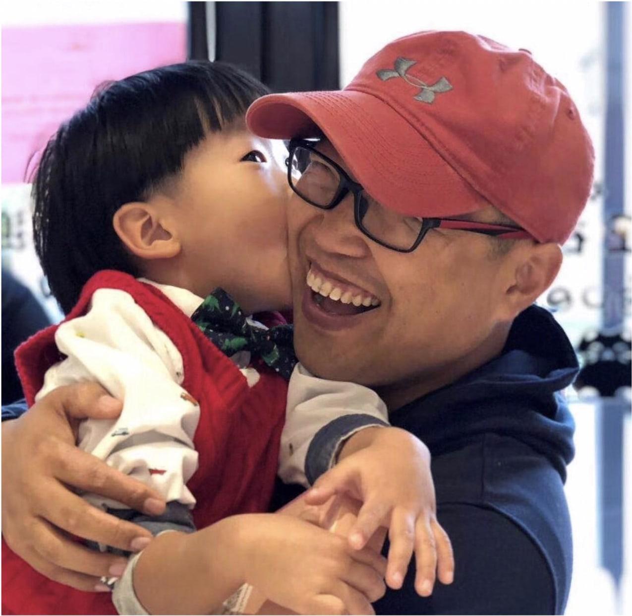 A little boy kisses his father