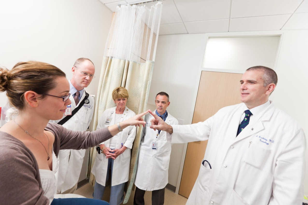 Three neuro-oncology physicians observing another neurooncology physician evaluating a patient