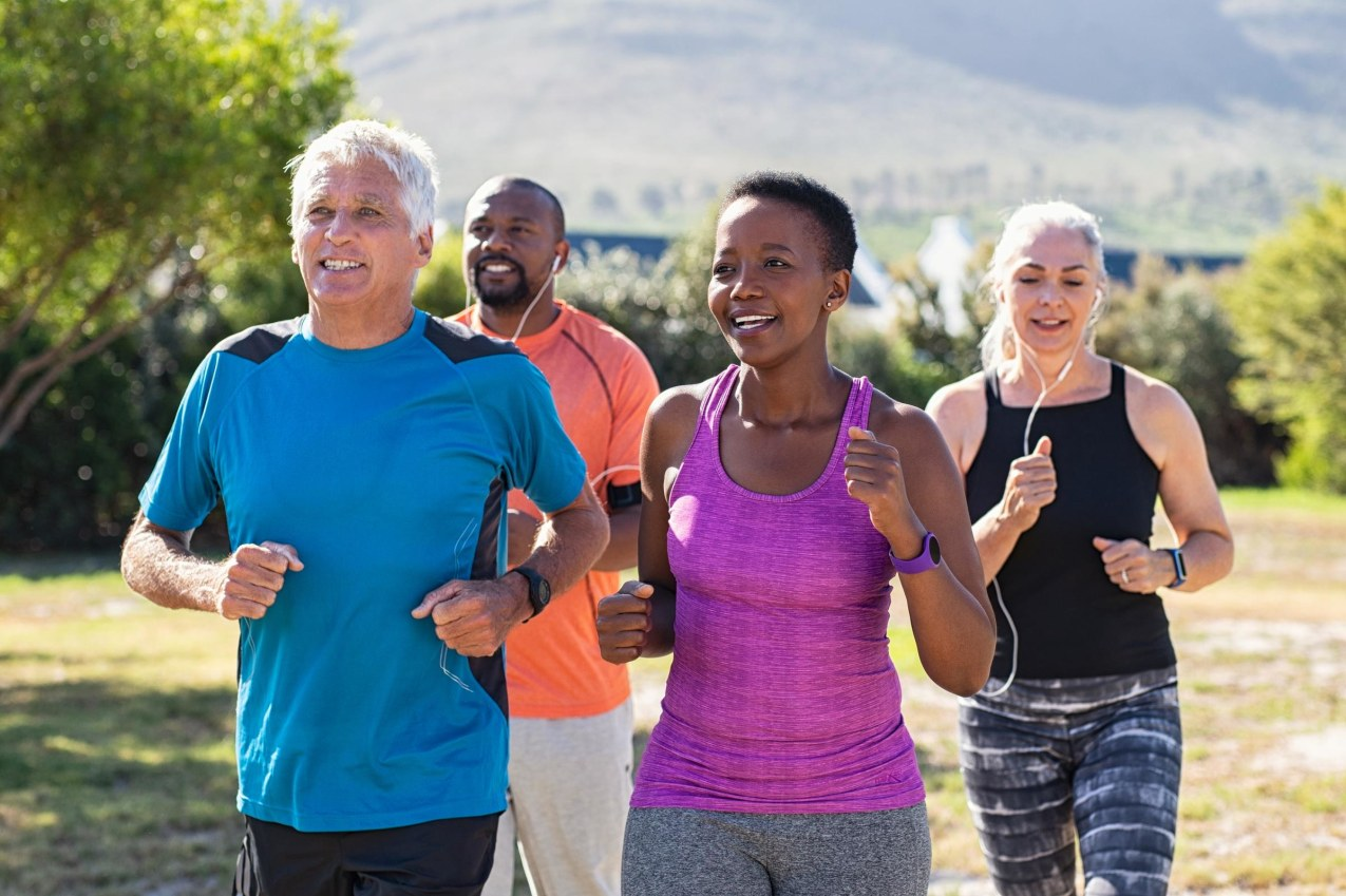 Healthy group of mature people jogging on track at park.