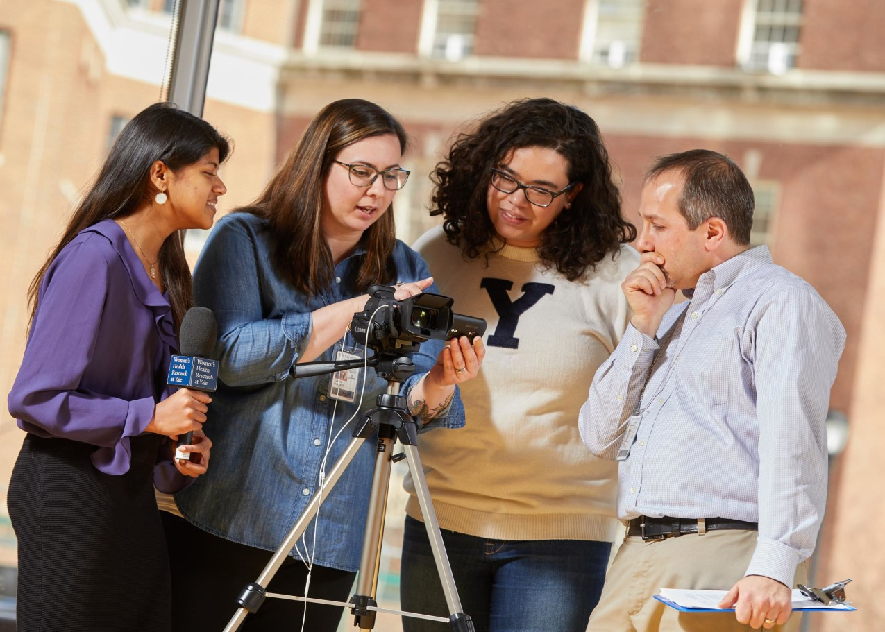 Undergraduate communications fellows reviewing video footage for a public awareness compaign.