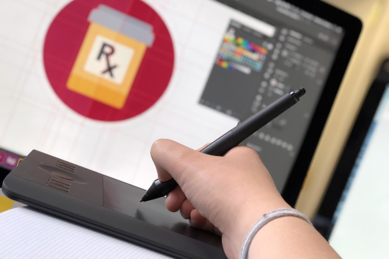 Close up of person using a drawing tablet with design software on a computer screen in the background