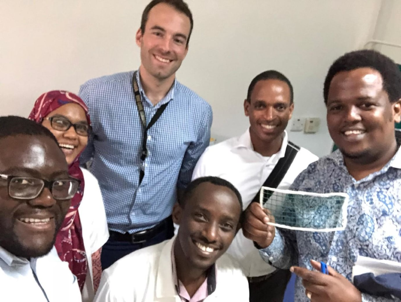 Drs. Kenedy Foryoung, Azza Naif, Fabian Laage Gaupp, Ivan Rukundo, Frank Minja, and Erick Mbuguje (from left to right) showcasing a self-made CT biopsy grid