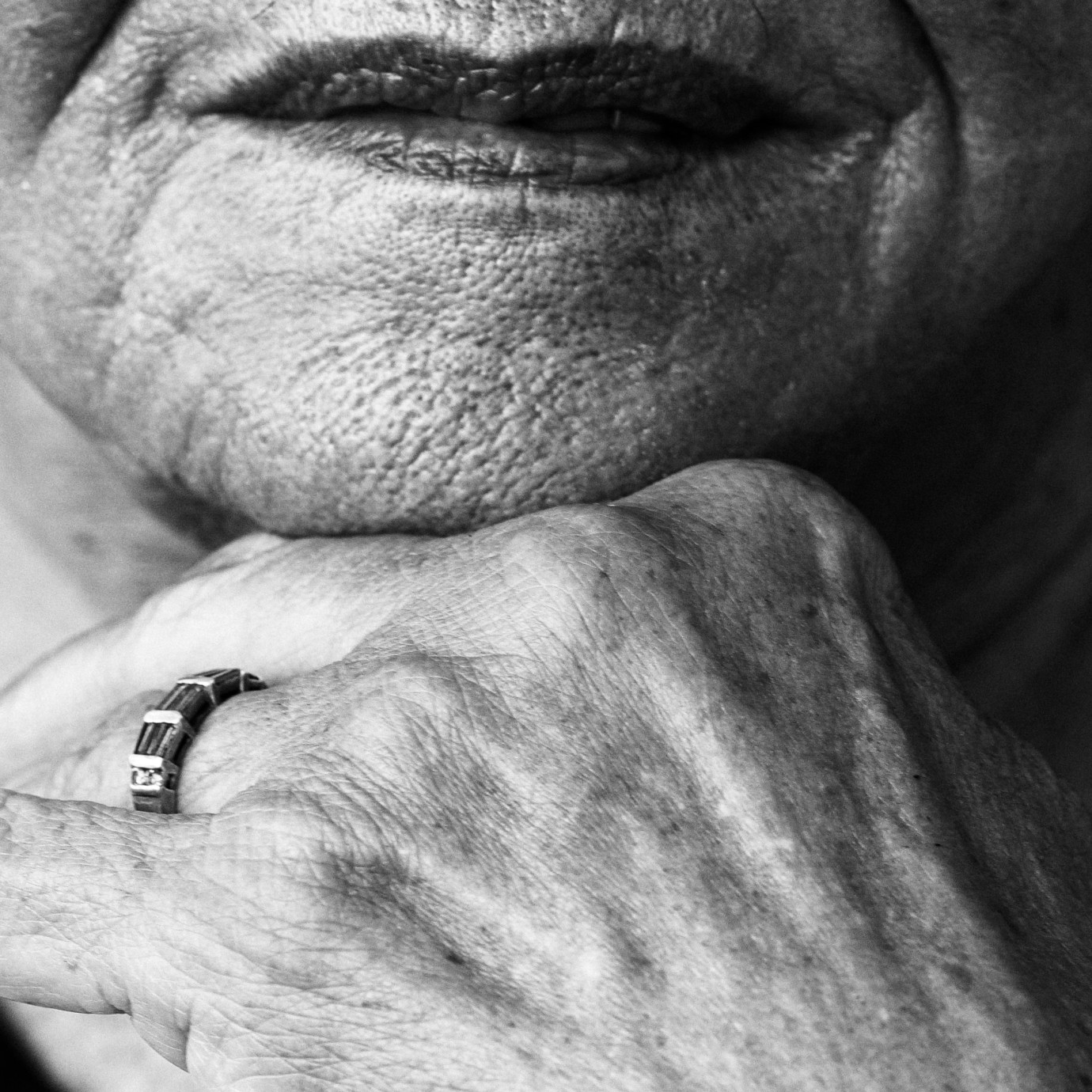Close up detail of hand on chin in black and white.