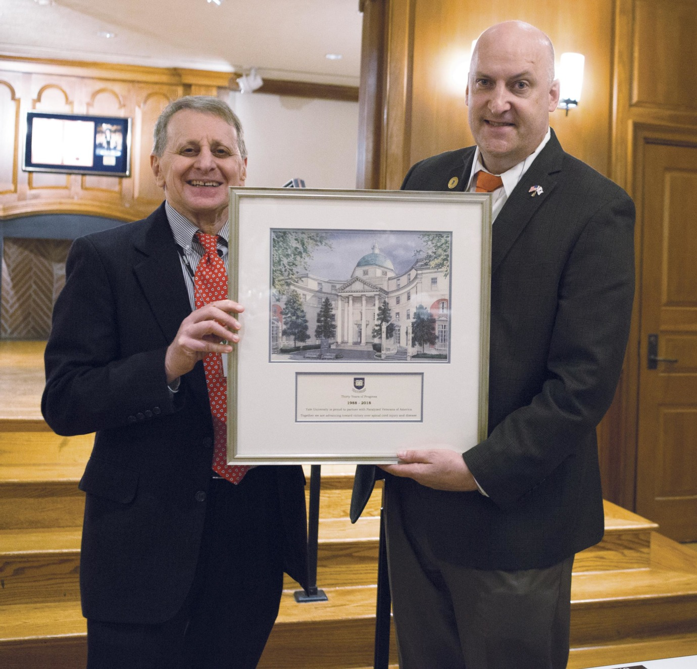 Stephen Waxman (left) and David Zurfluh display a print that celebrates the 30-year partnership between Yale and Paralyzed Veterans of America