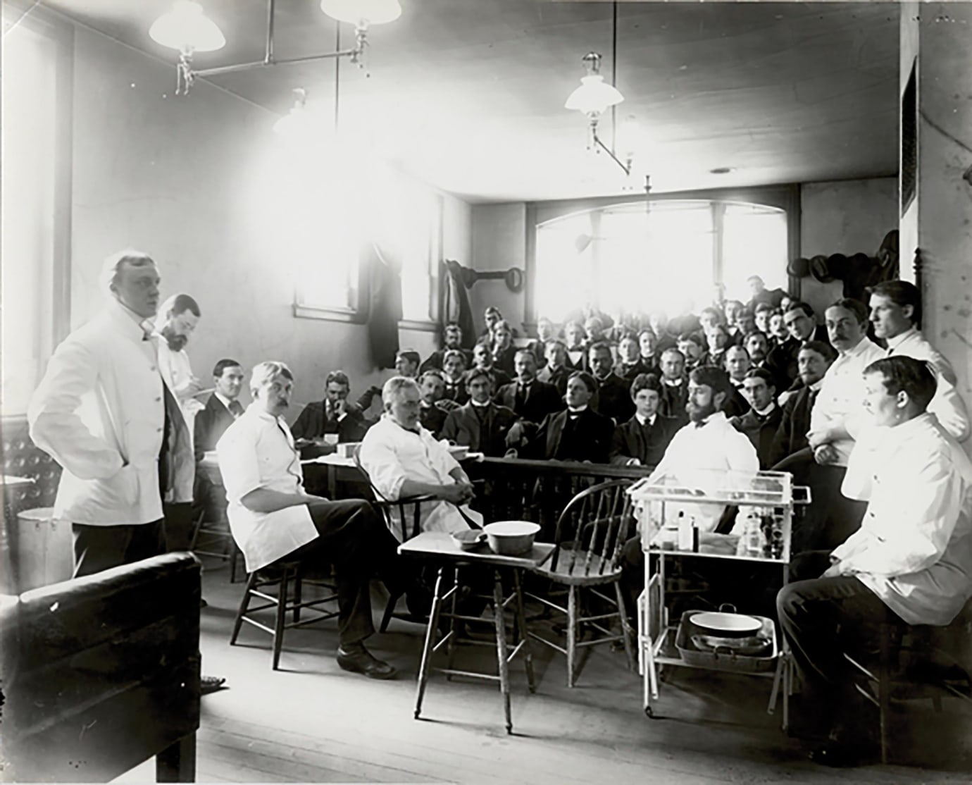 In this photo, taken around 1900, the legendary surgeon and medical educator William Carmalt (standing at left) lectures at the medical school