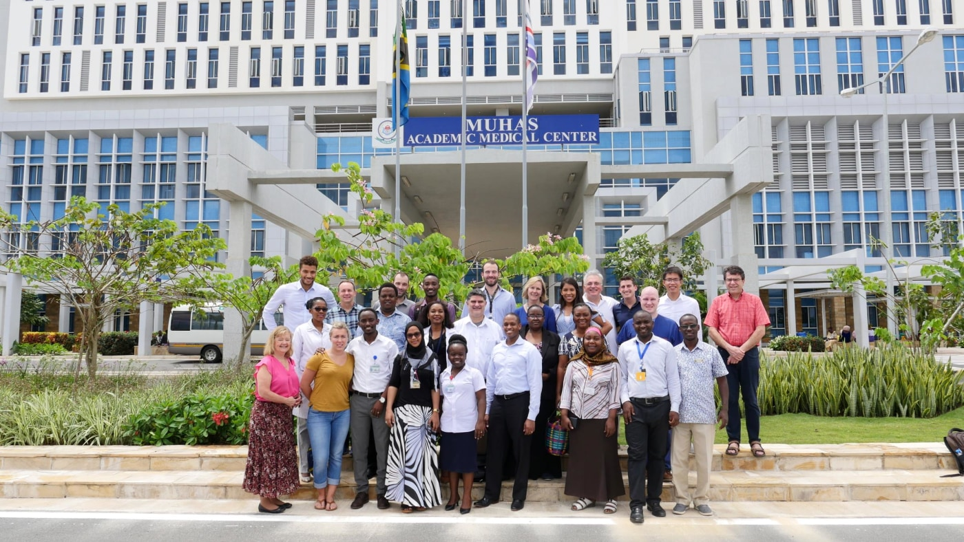 Group photo in front of the MNH Mloganzila campus with faculty, nurses, technologists, residents and medical students from Muhimbili, the US, and Germany.