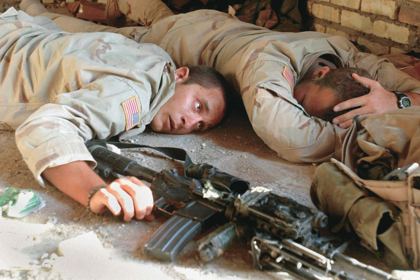 A soldier covers his head while another remains alert during an August 2004 battle with Shiite militias in the holy city of Najaf.