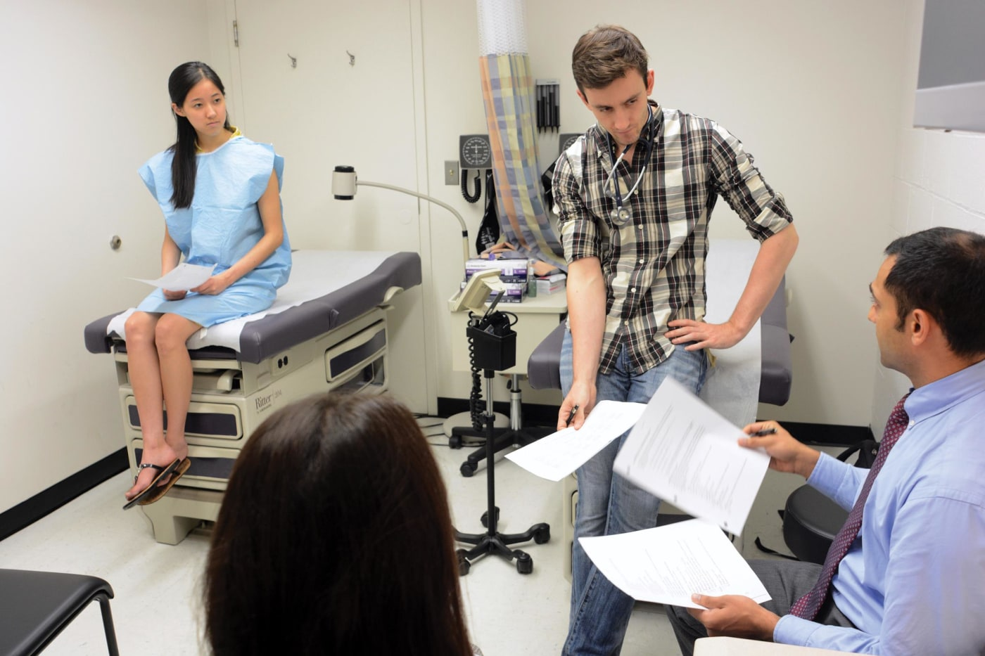 In the clinical exam room, Emily Yin role-played a patient while Radovan Vasic conducted an exam and Amit Mittal observed. Marina di Bartolo, a medical student in her final year, supervised the session.