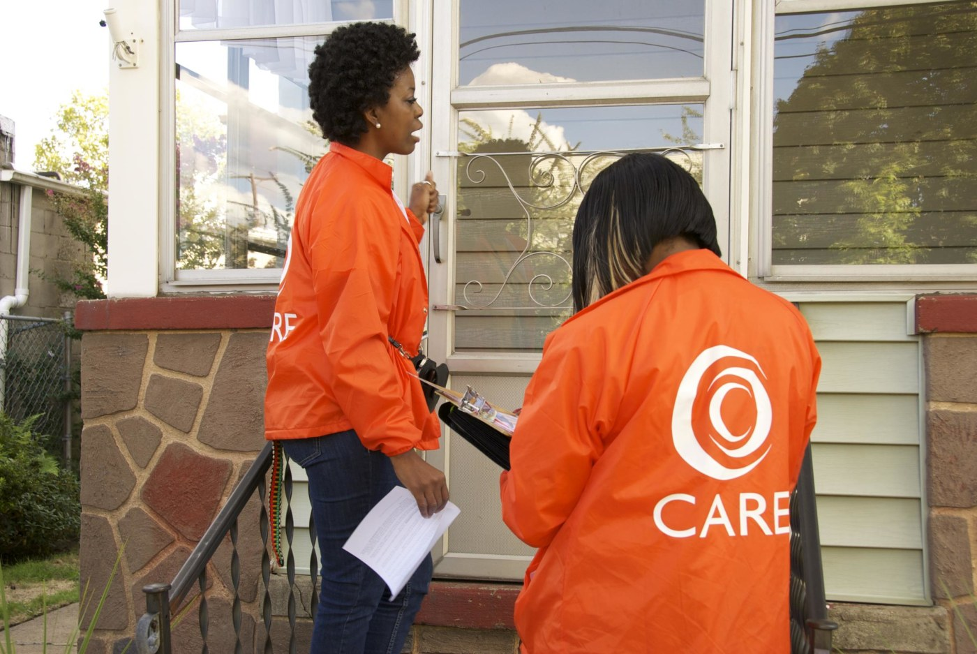 Community Health Workers knock on a door