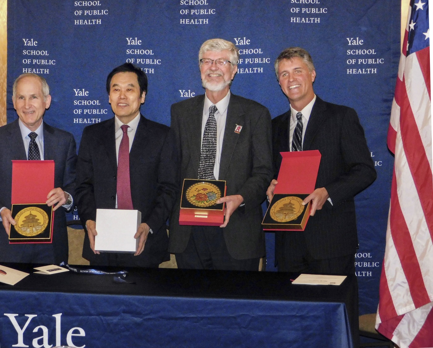 Representatives from Yale and the National Cancer Center of China exchange gifts during official signing ceremony.