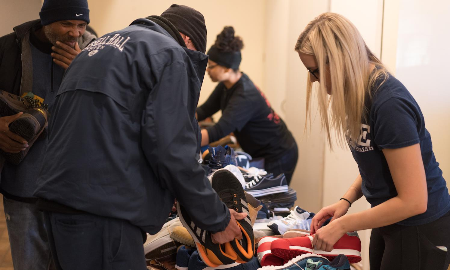 Two men selecting sneakers and a student helping them.